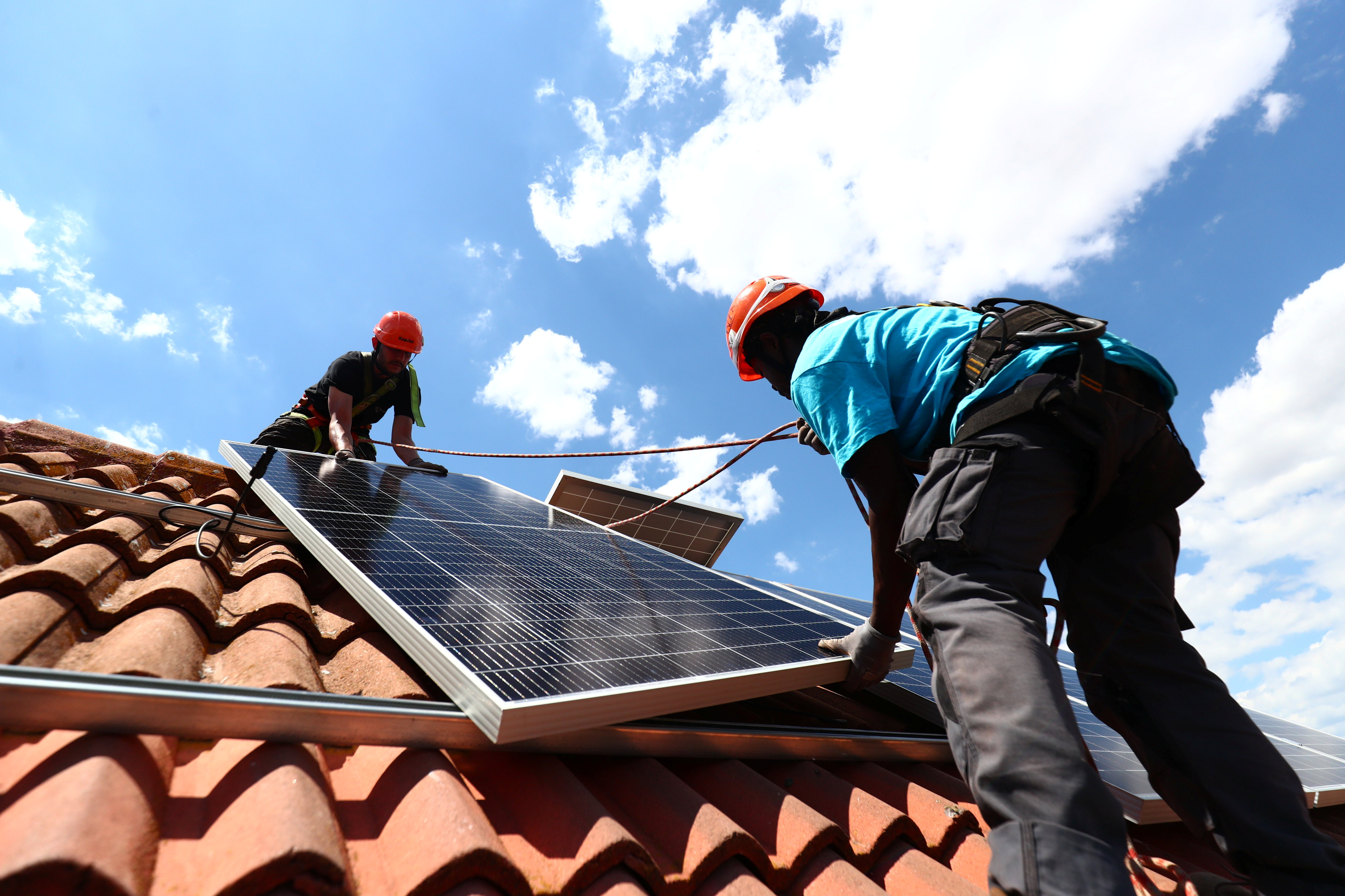 Rodrigue Kauahou and Jose Carlos Navarro, workers of the installation company Alromar, set up solar panels on the roof of a home in Colmenar Viejo, Spain June 19, 2020. Picture taken June 19, 2020. REUTERS/Sergio Perez - RC2HPH9WJ274