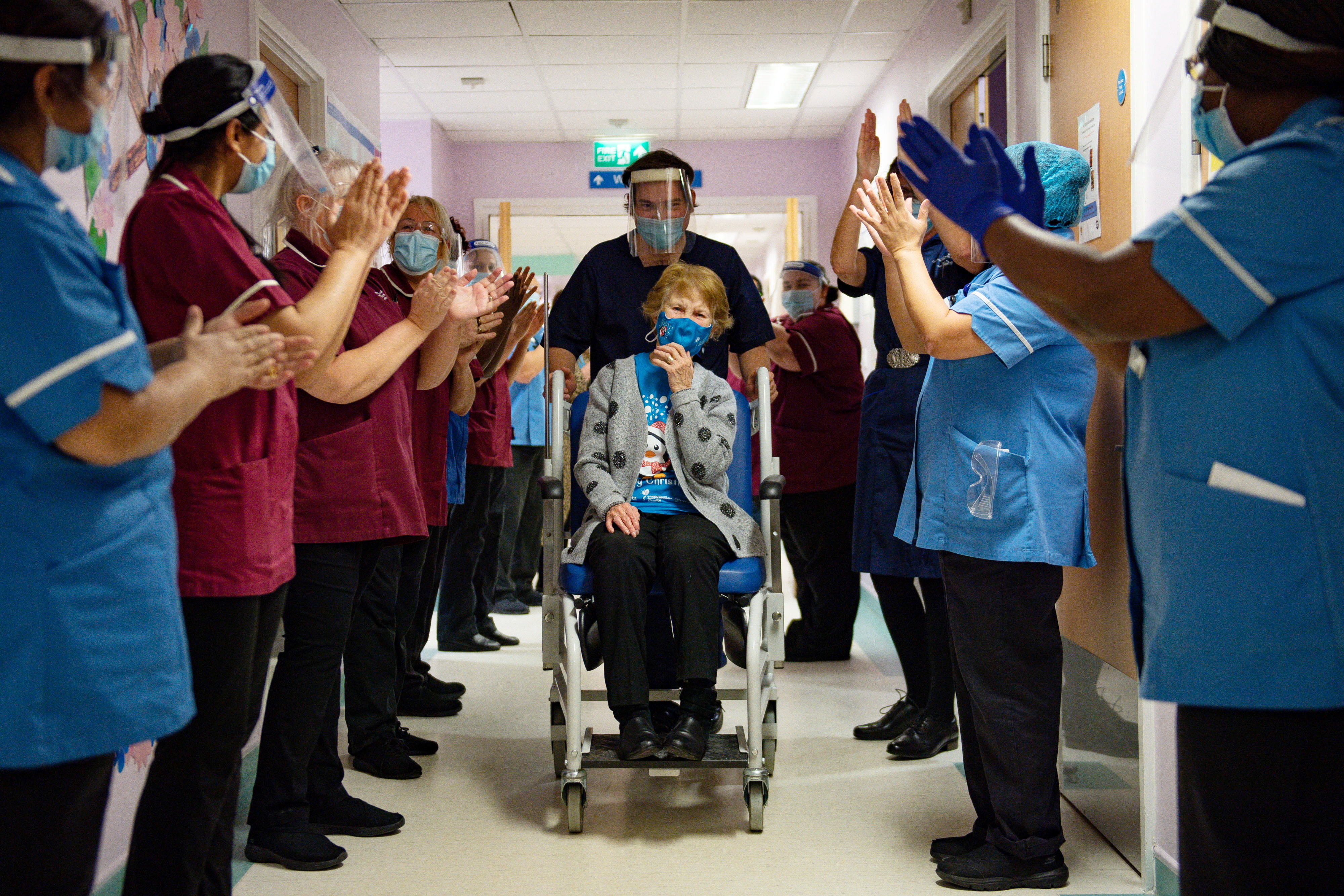 Margaret Keenan, 90, is applauded by staff as she returns to her ward after becoming the first person in Britain to receive the Pfizer/BioNTech  COVID-19 vaccine at University Hospital, at the start of the largest ever immunisation programme in the British history, in Coventry, Britain December 8, 2020. Britain is the first country in the world to start vaccinating people with the Pfizer/BioNTech jab. Jacob King/Pool via REUTERS - RC2XIK9QQQM7