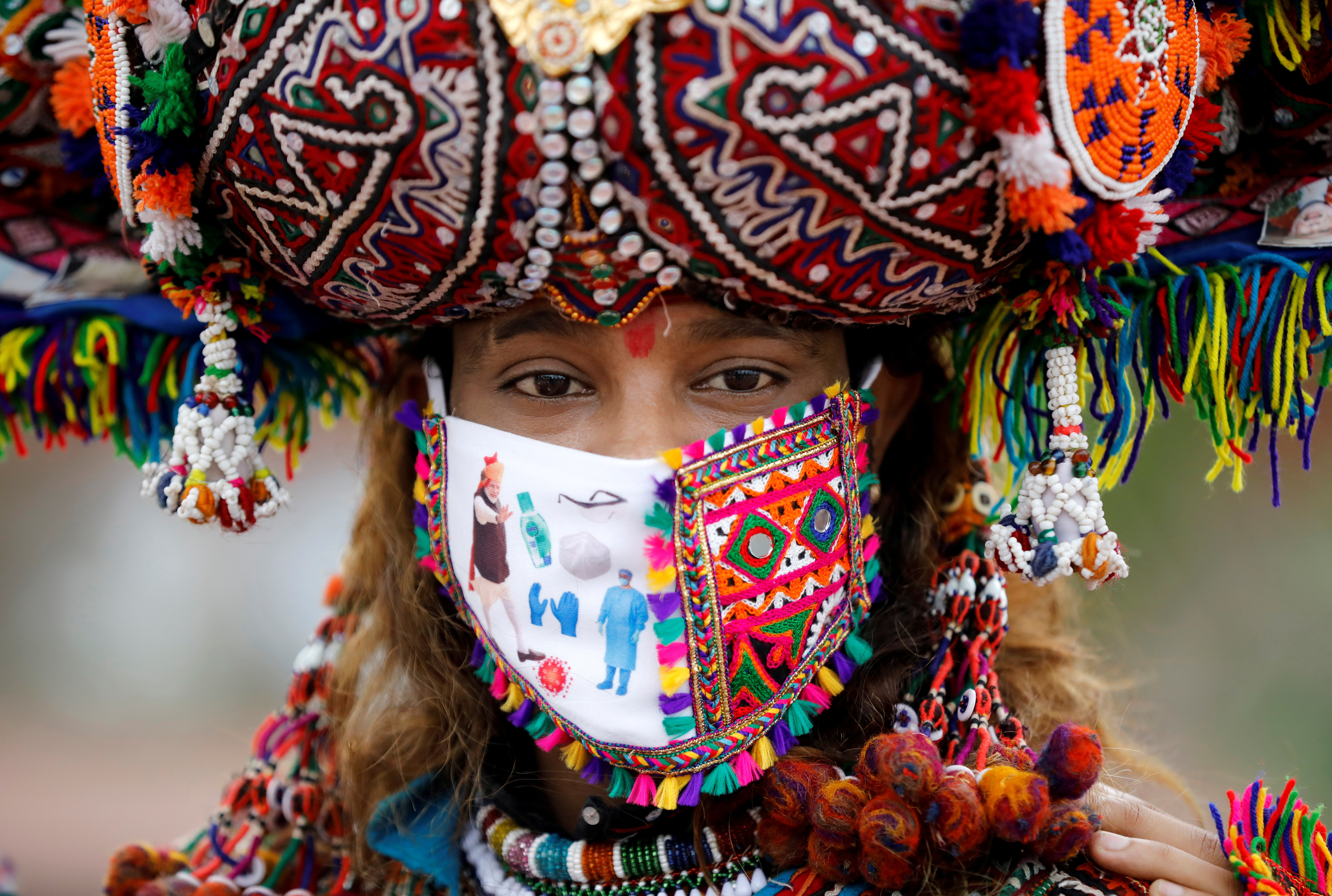 A participant in a traditional costume wearing a face mask attends a rehearsal for Garba, a folk dance, ahead of Navratri, a festival during which devotees worship the Hindu goddess Durga and youths dance in traditional costumes, amidst the coronavirus disease (COVID-19) outbreak, in Ahmedabad, India, September 12, 2020. REUTERS/Amit Dave     TPX IMAGES OF THE DAY - RC2UWI9DC85L