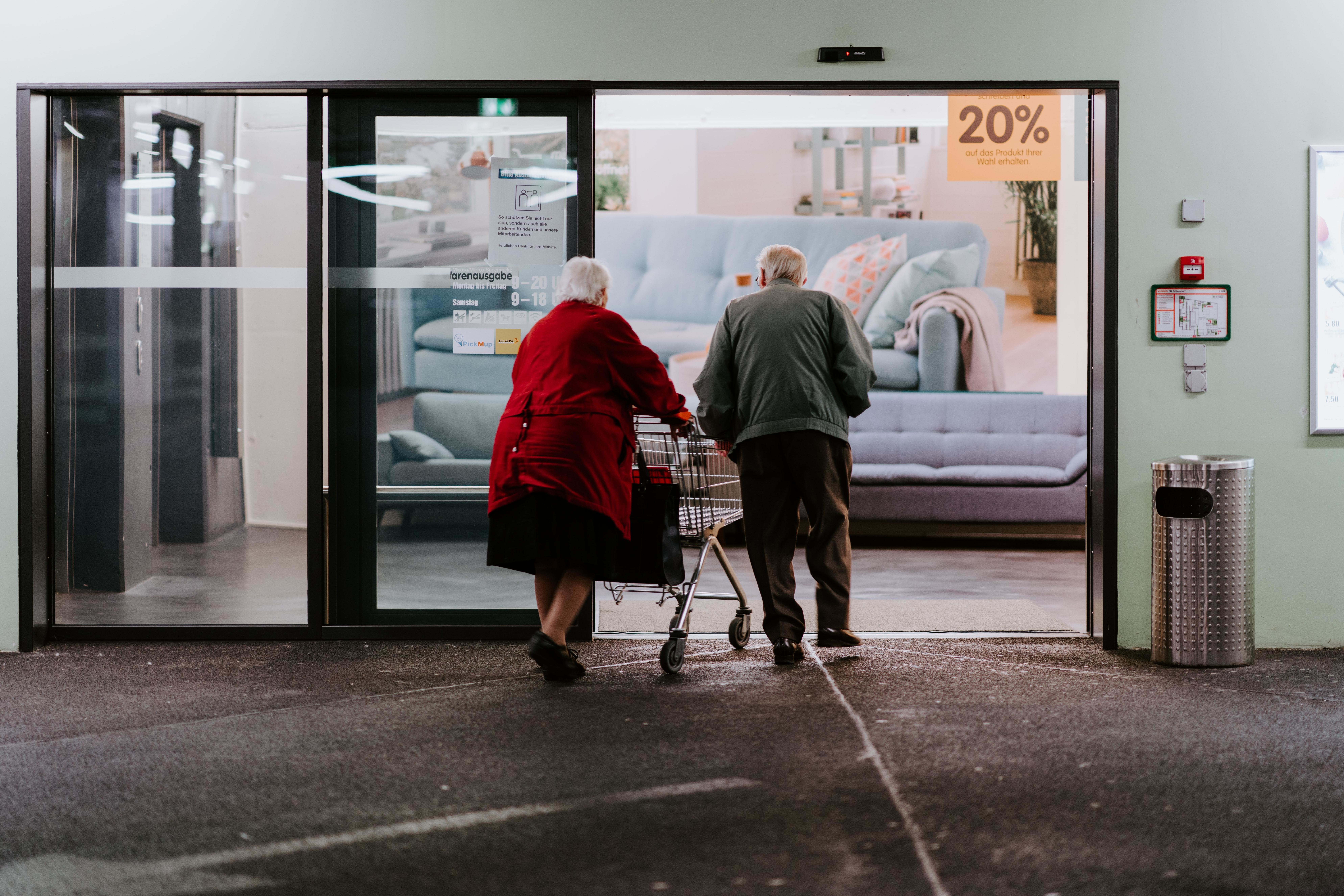 Two older adults enter a shop with a shopping trolley