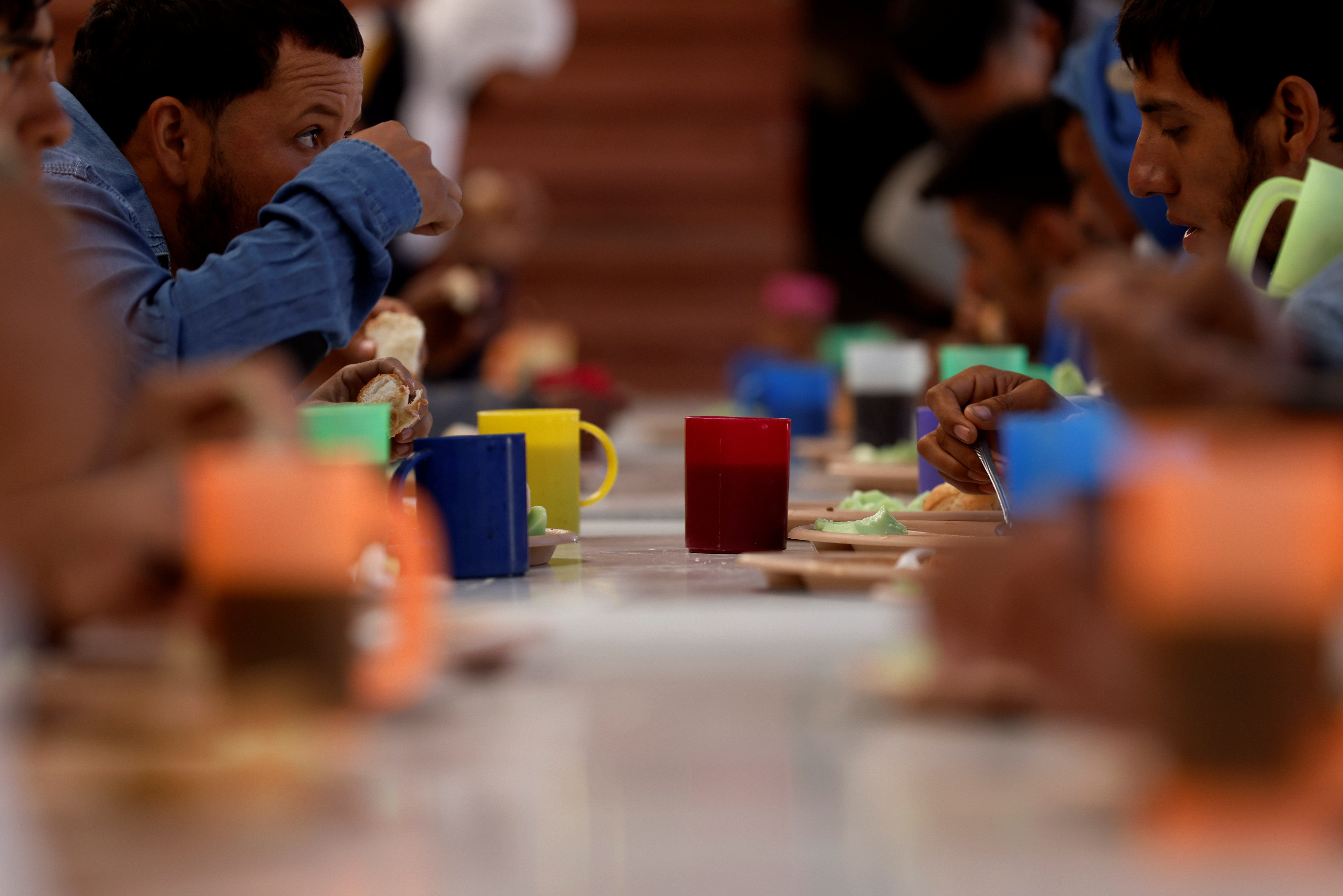 """Central American migrants eat donated food inside the """"Sacred Family"""" shelter as they make the perilous journey north to the United States, in Apizaco, Tlaxcala, Mexico April 16, 2021. Picture taken April 16, 2021."""