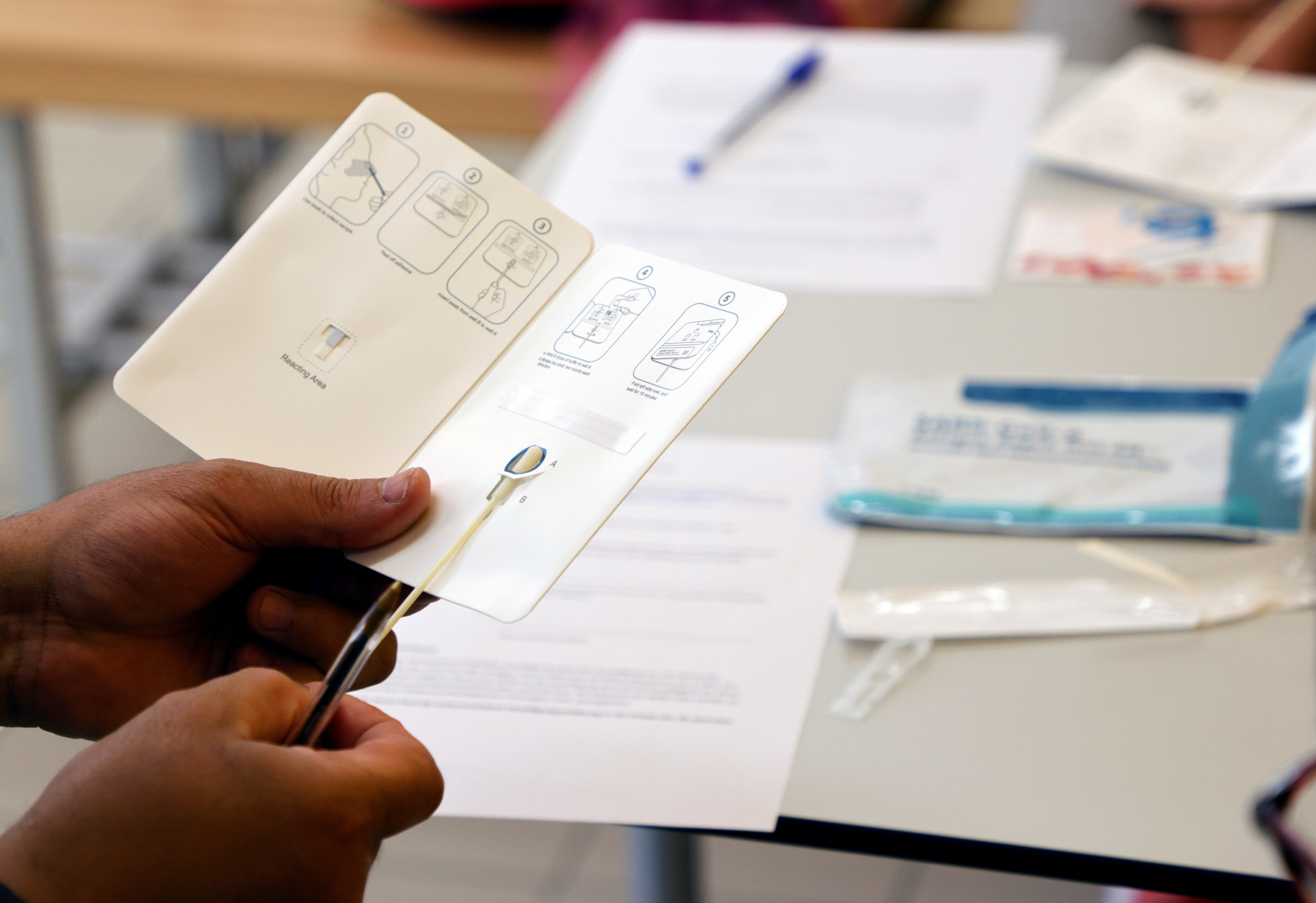A person holds a coronavirus (COVID-19) rapid antigen test in a primary school, as Austrian schools open for pupils after summer holidays, in Vienna, Austria, September 6, 2021. REUTERS/Leonhard Foeger - RC28KP91JPFJ