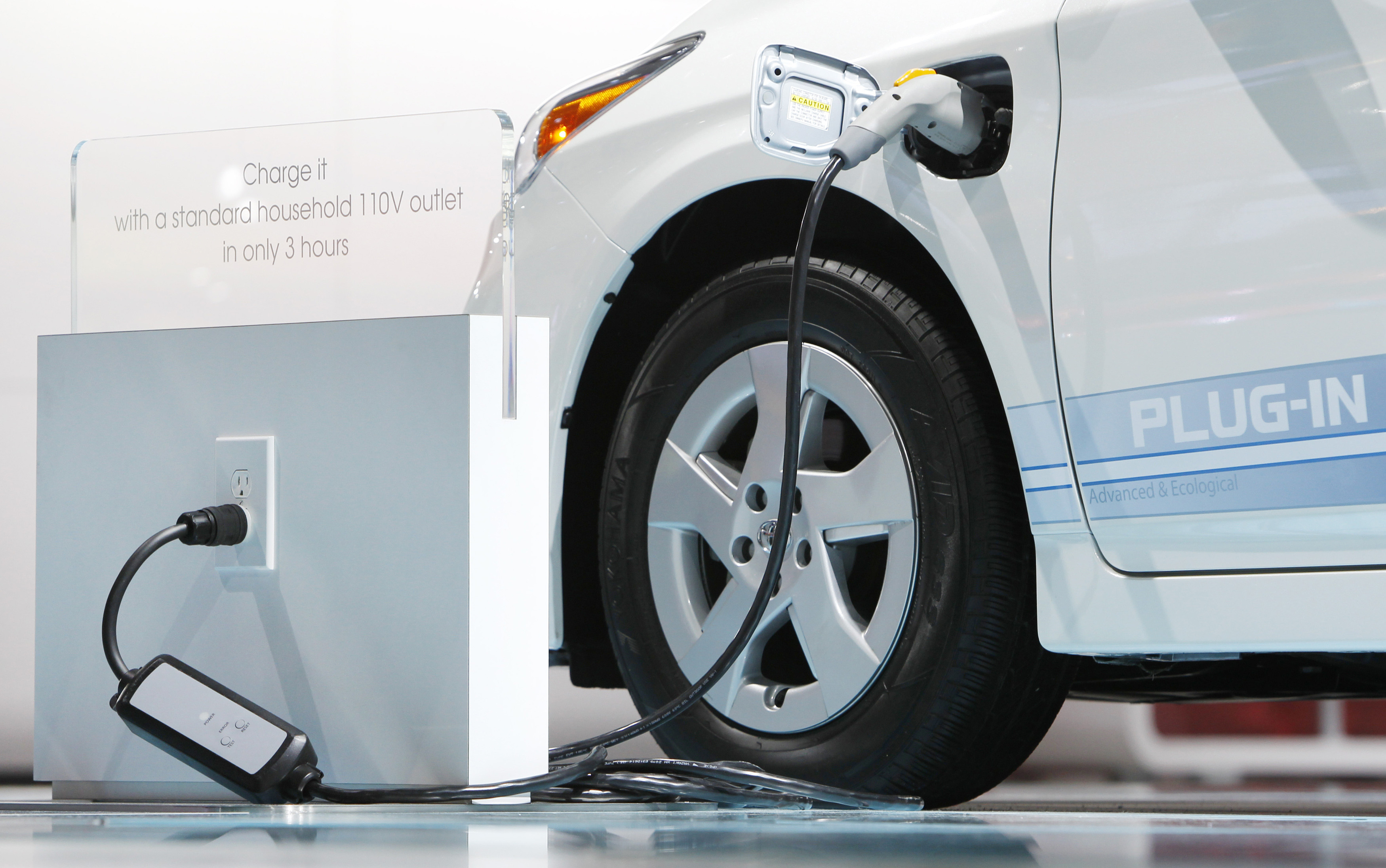 an electric car is seen plugged into a wall