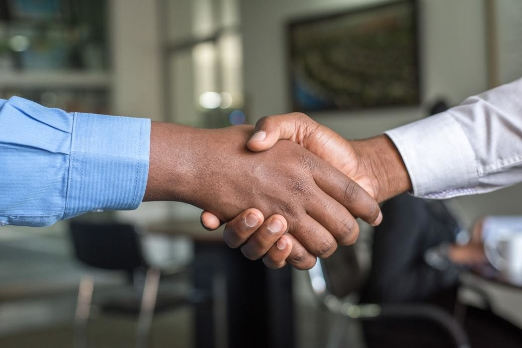 The hands and forearms of two people are seen pictured in a handshake.