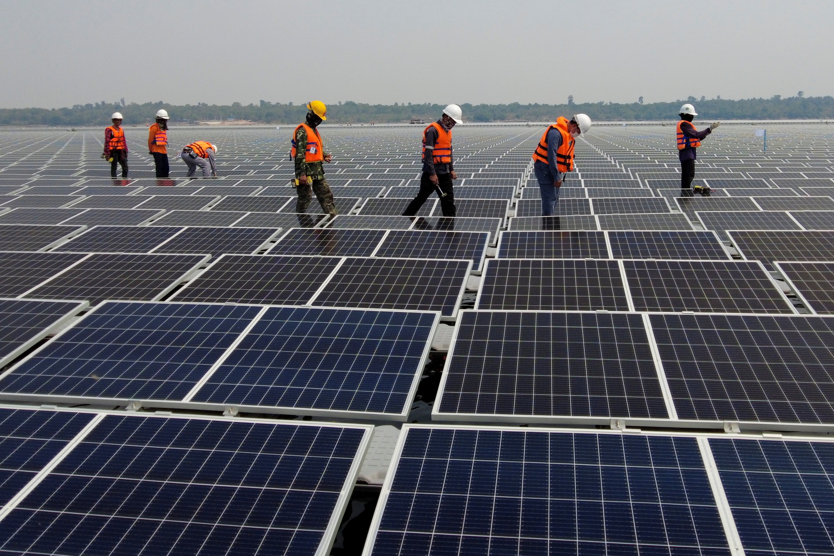 image of workers walking between solar cell panels over the water surface of Sirindhorn Dam in Ubon Ratchathani, Thailand.