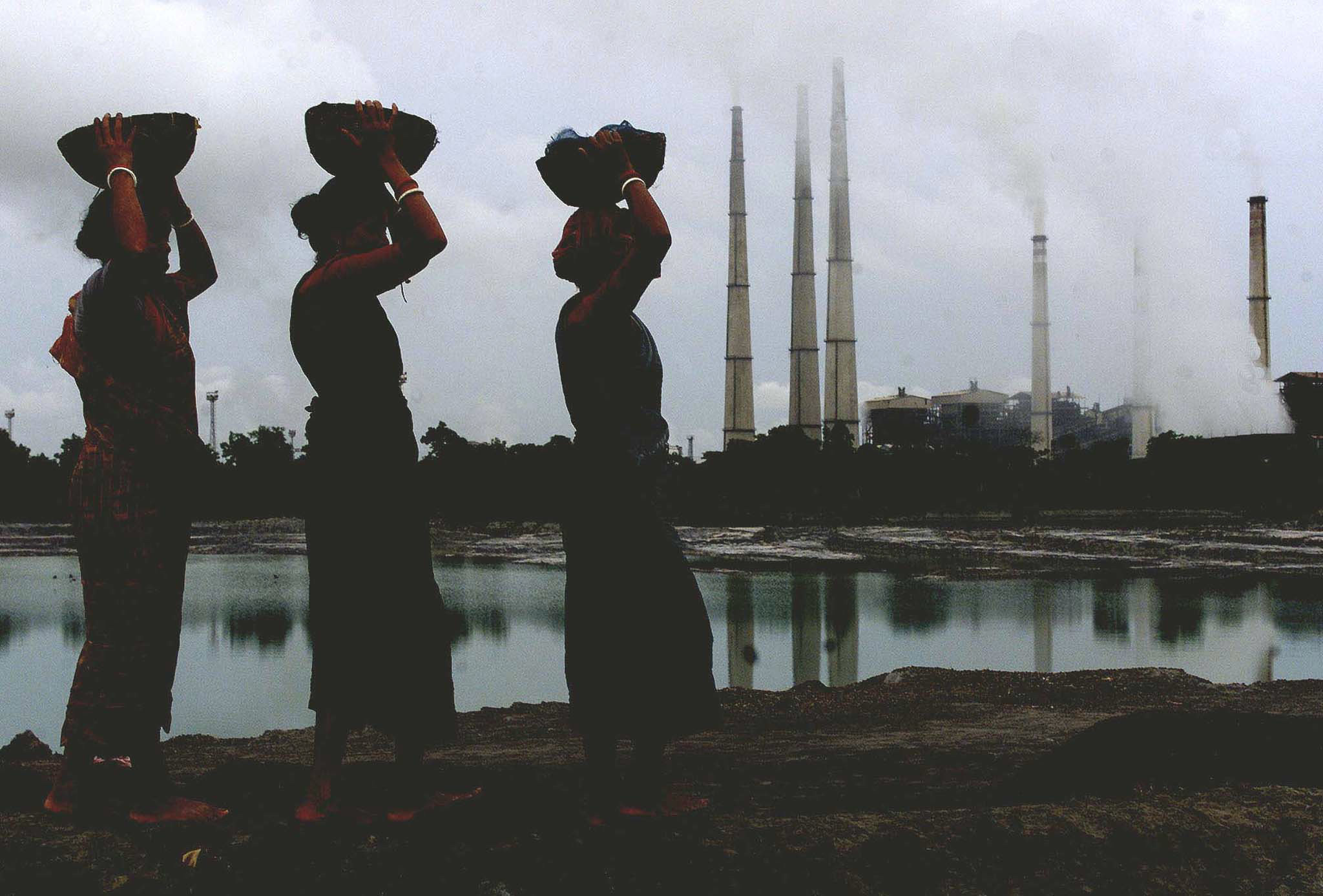 Indian female labourers carry small pieces of coal deposit from liquidash generated from a thermal power plant