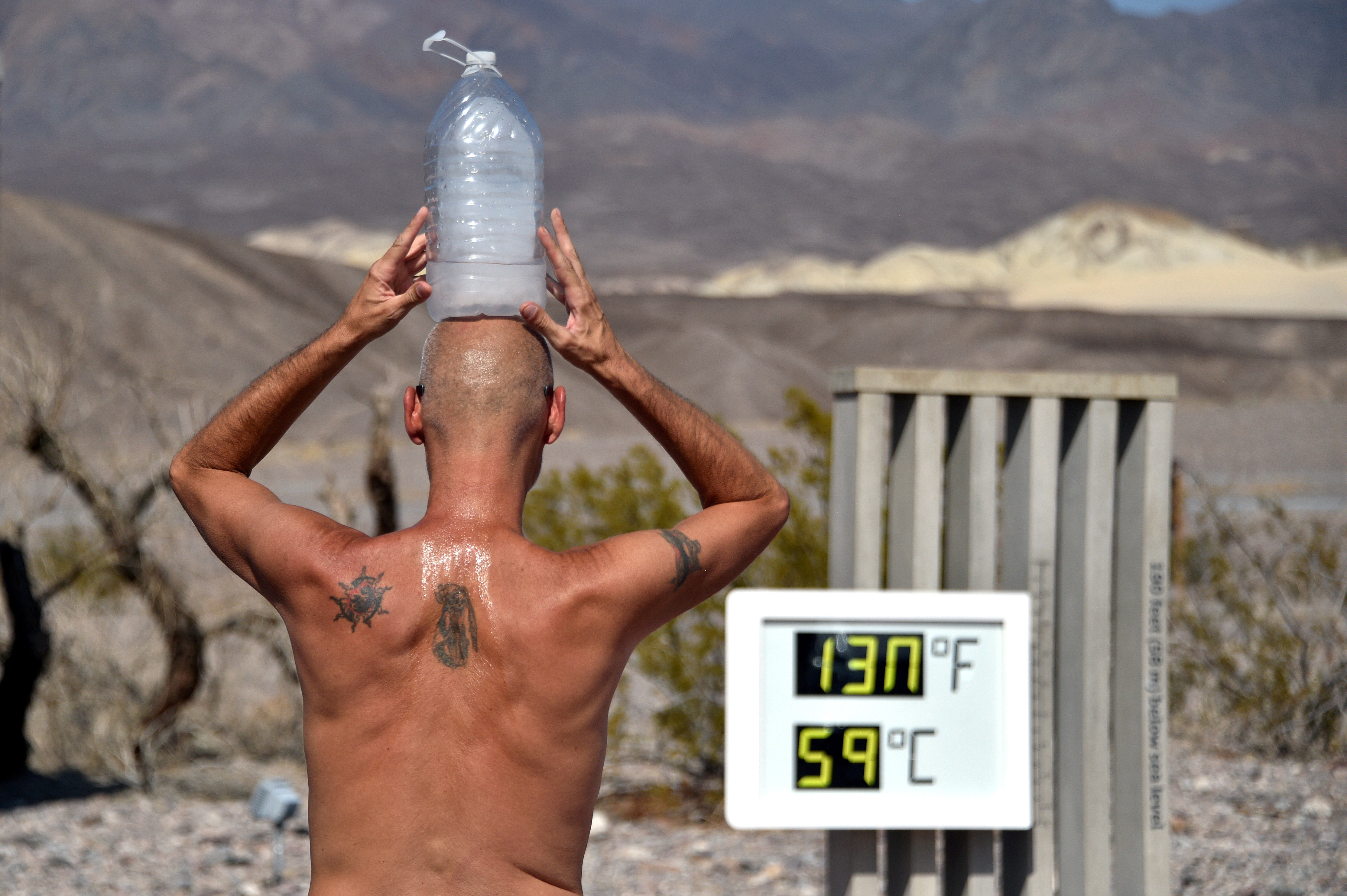 Steve Krofchik of Las Vegas keeps cool with a bottle of ice on his head as the unofficial thermometer reads 130 degrees Fahrenheit (54.4 Celsius), with a mechanical fault on the display which causes the numbers to render incorrectly, at the Furnace Creek Visitors Center in Death Valley, California, U.S. August 17, 2020. REUTERS/David Becker     TPX IMAGES OF THE DAY - RC20GI9I0D6I