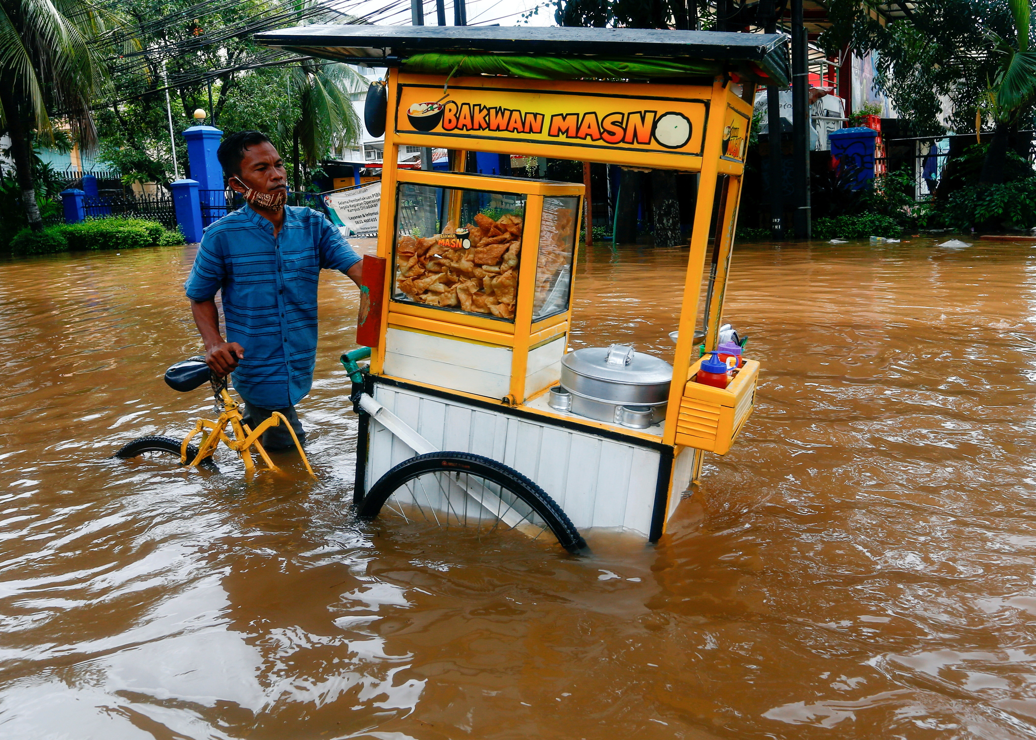 A street vendor pushes his cart through the water in an area affected by floods following heavy rains in Jakarta, Indonesia, February 20, 2021. REUTERS/Ajeng Dinar Ulfiana     TPX IMAGES OF THE DAY - RC27WL9PY0L8