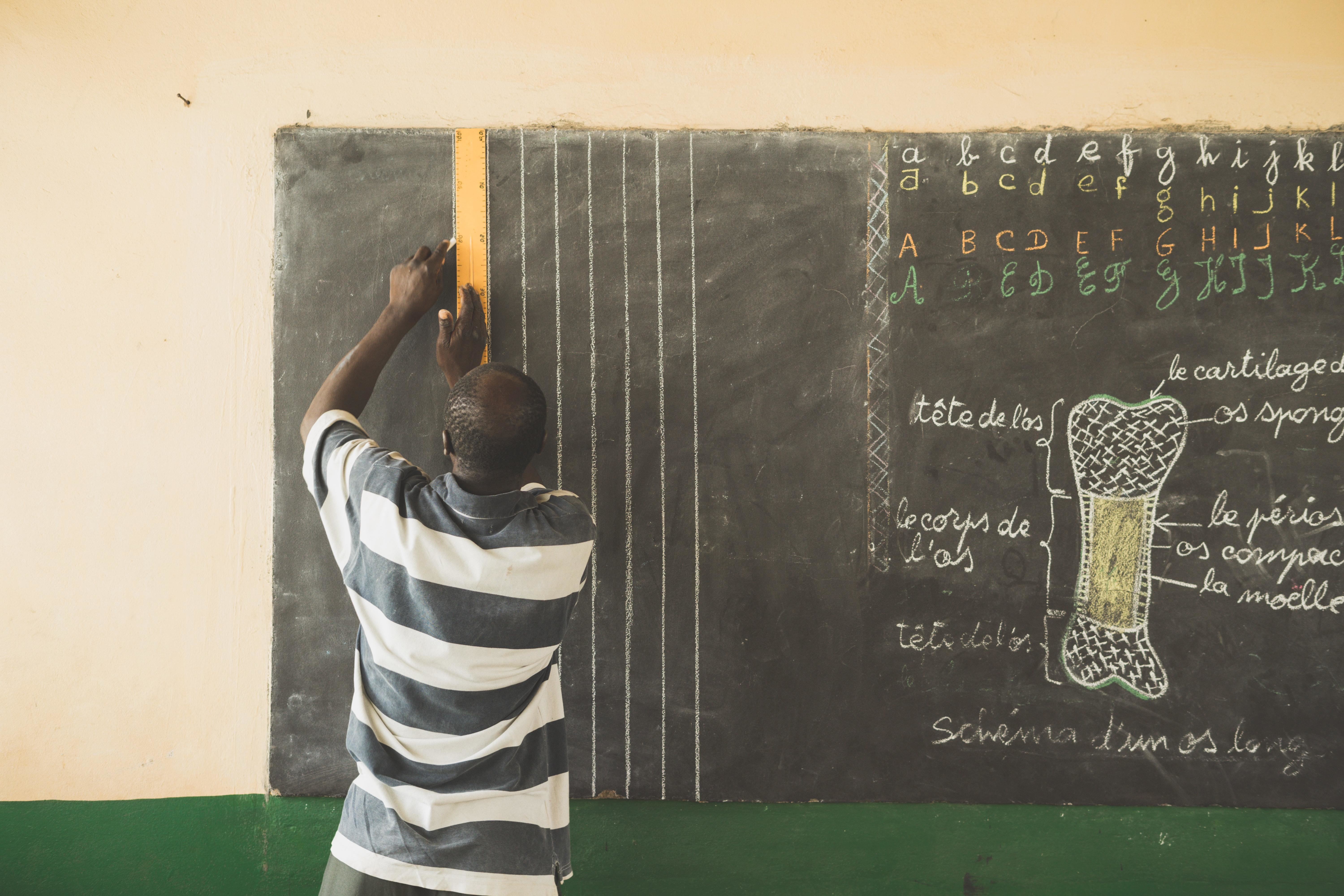 A man in a black and white shirt writing on a chalk board
