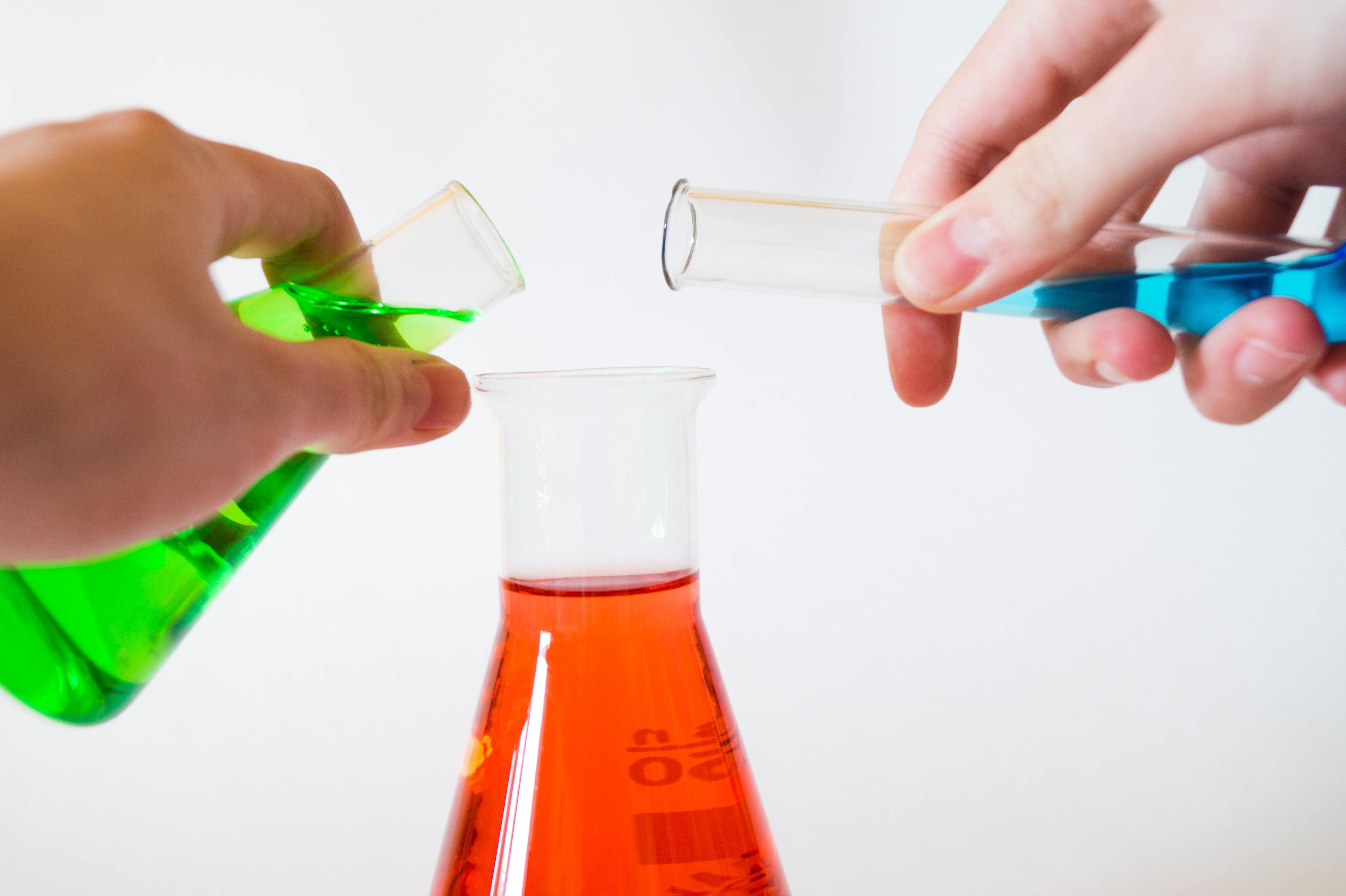 Hands holding laboratory flasks