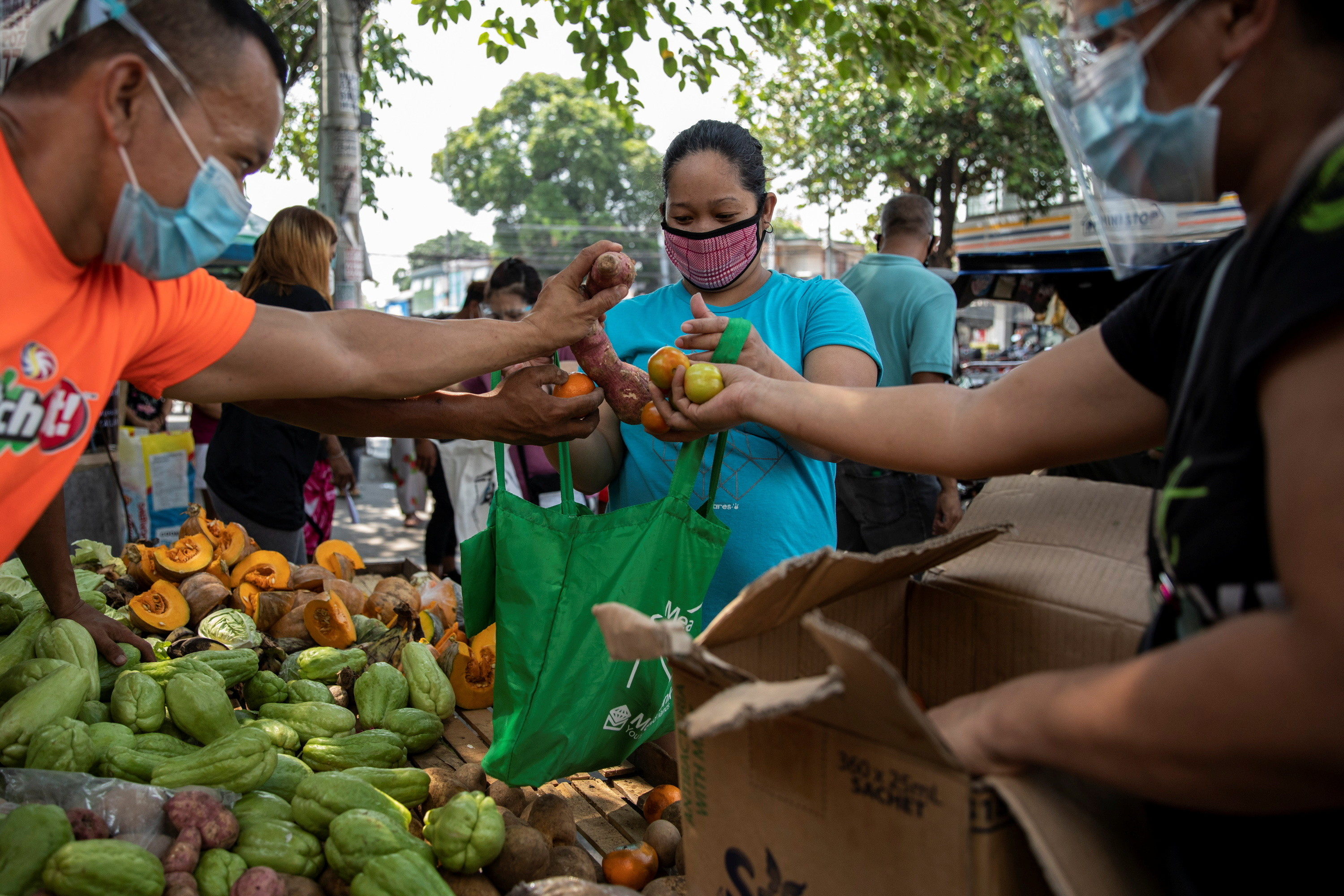 a woman receives free fruits and vegetables from a community pantry amid the coronavirus disease (COVID-19) outbreak, in Quezon City, Metro Manila, Philippines, April 23, 2021