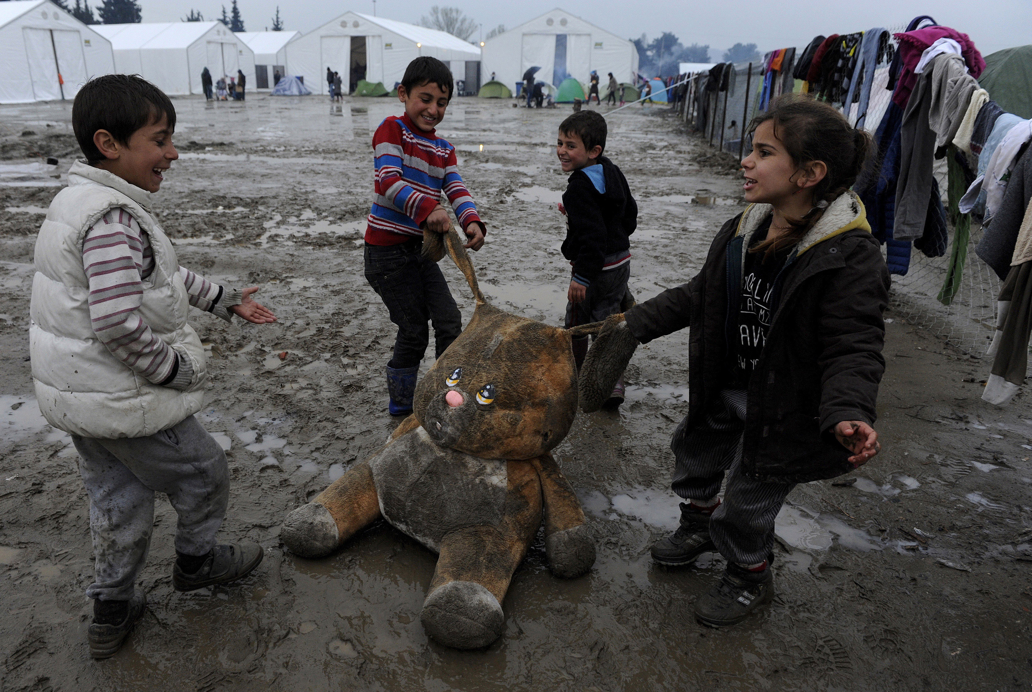 Refugee children play with a stuffed toy at a muddy makeshift camp at the Greek-Macedonian border, near the village of Idomeni, Greece March 15, 2016. REUTERS/Alexandros Avramidis      TPX IMAGES OF THE DAY - GF10000346539