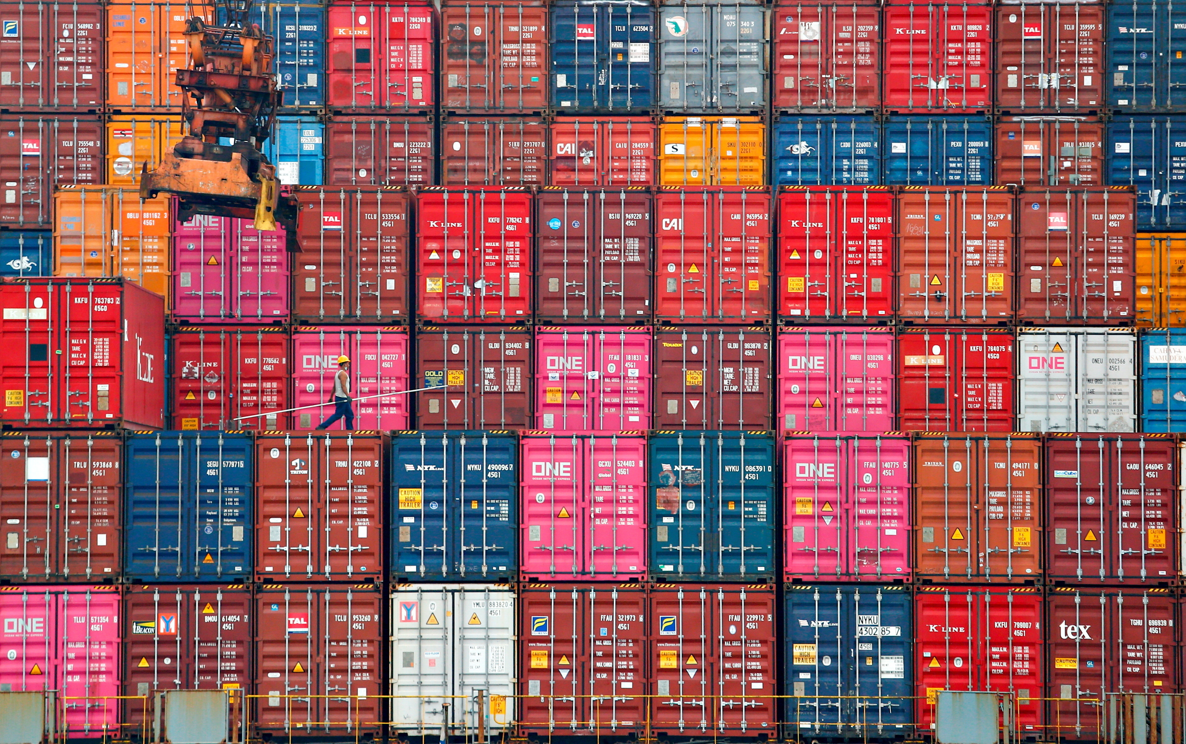 A worker walks on stacks of containers at the Tanjung Priok port in Jakarta, Indonesia, January 22, 2021. REUTERS/Ajeng Dinar Ulfiana     TPX IMAGES OF THE DAY - RC2WCL9EYDE4