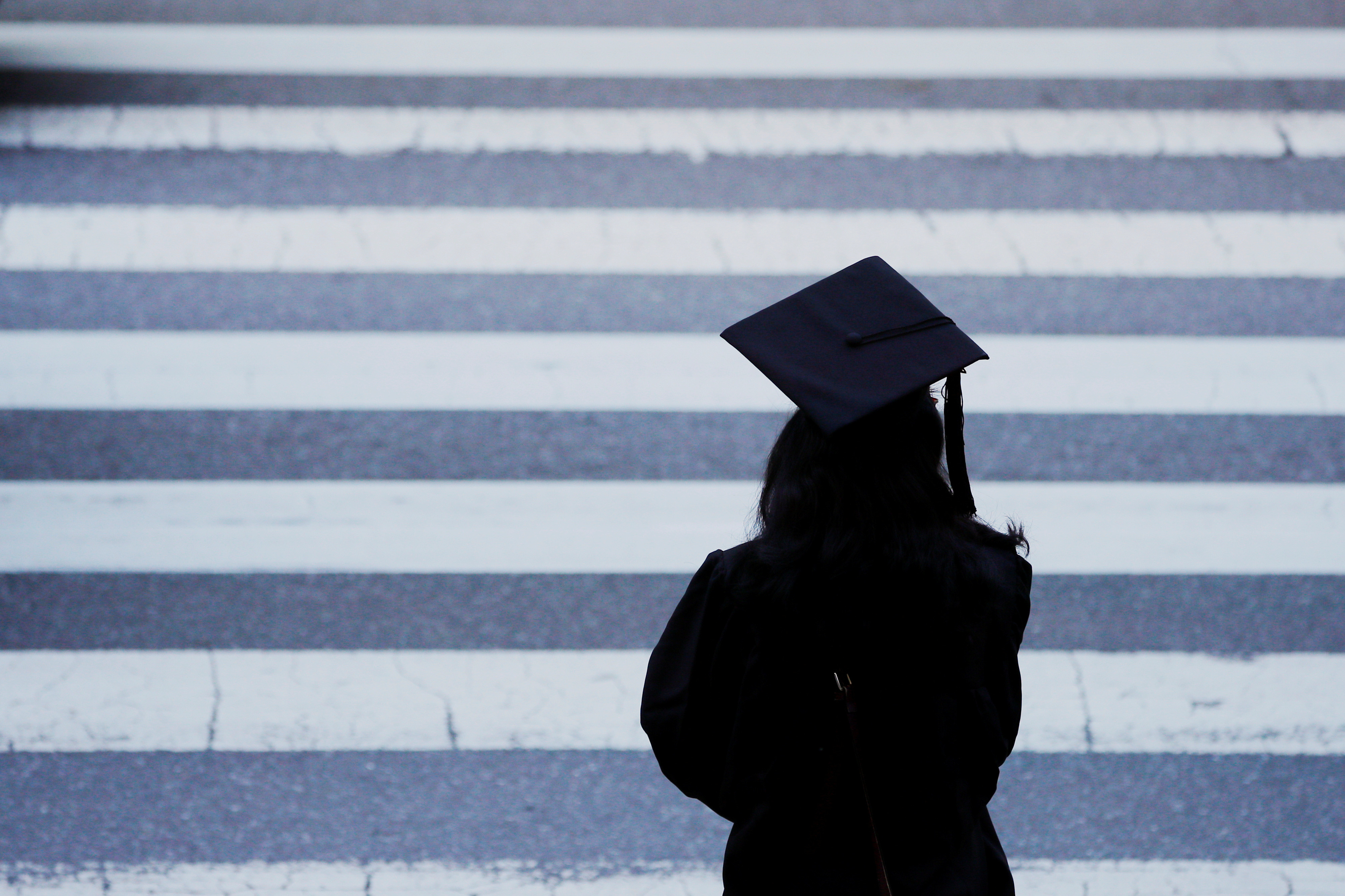 A graduating student waits to cross the street before Commencement Exercises at the Massachusetts Institute of Technology (MIT) in Cambridge, Massachusetts, U.S., June 7, 2019.   REUTERS/Brian Snyder - RC15B2D28AF0