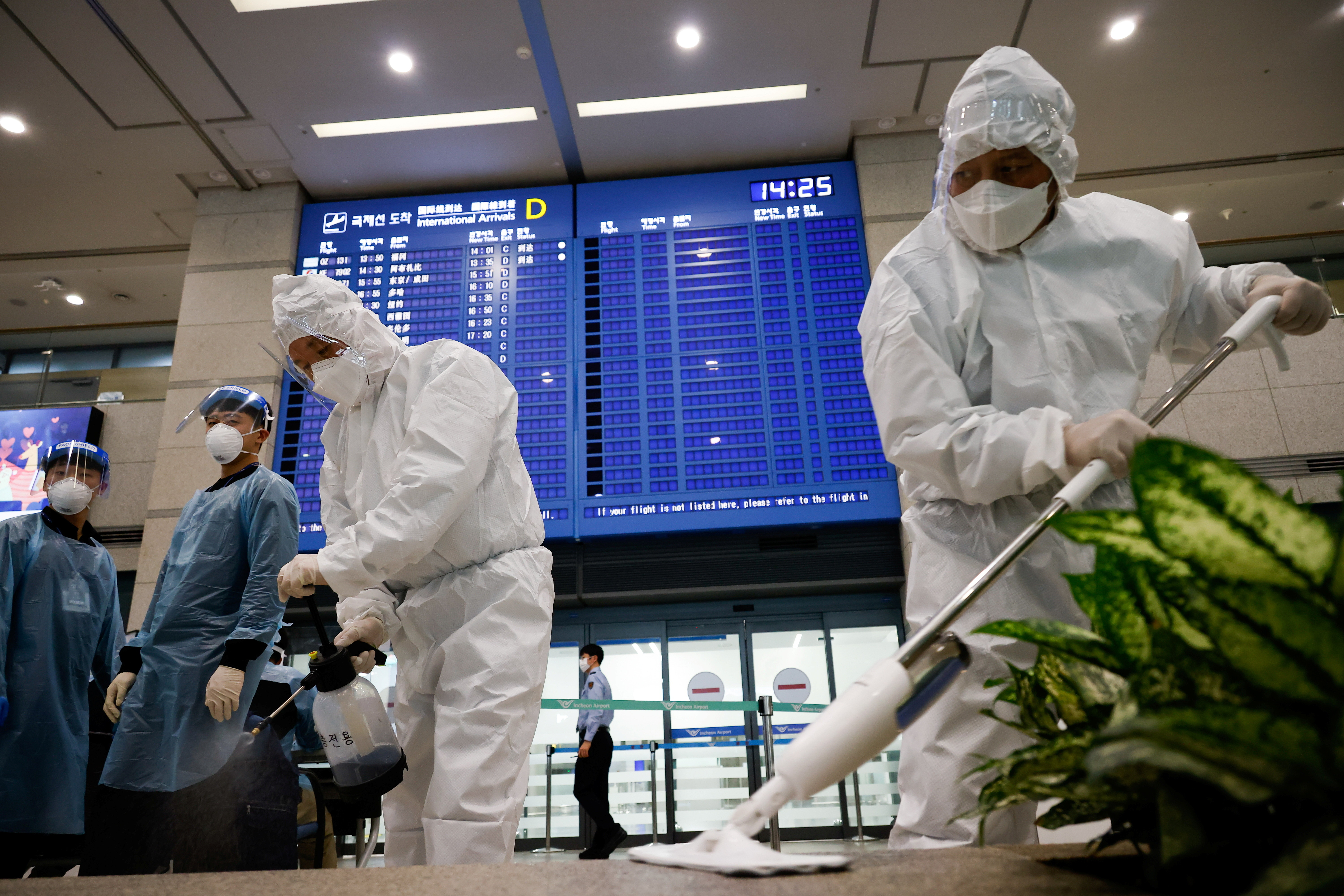 Workers wearing protective gear disinfect an arrival gate as an electronic board shows arrivals' information amid the coronavirus disease (COVID-19) pandemic at the Incheon International Airport in Incheon, South Korea, December 28, 2020. REUTERS/Kim Hong-Ji - RC27WK9DVM1P