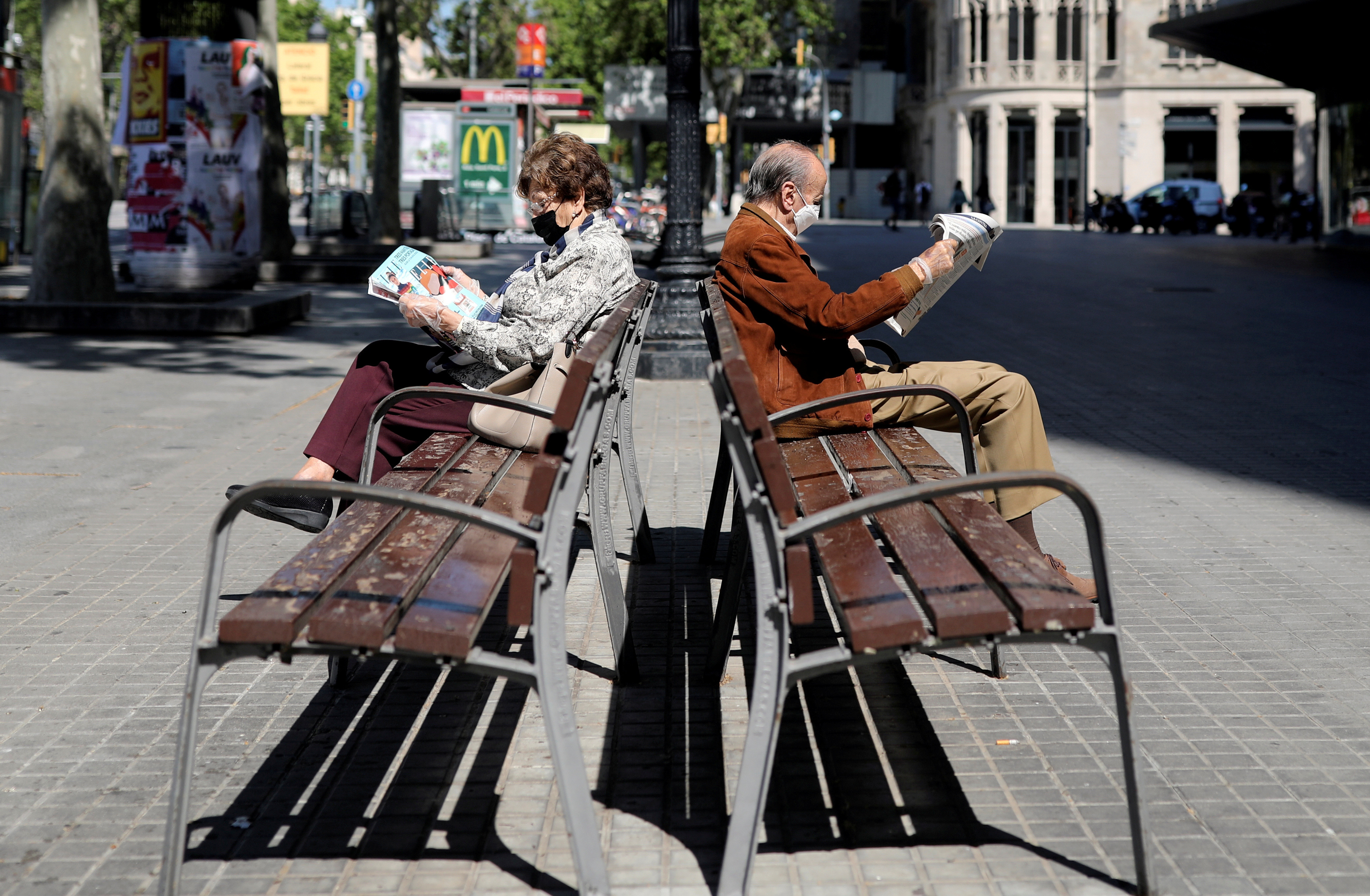 Elderly people wearing protective masks read newspapers as they sit on benches, during the hours in which the elderly are allowed to be outdoors, amid the coronavirus disease (COVID-19) outbreak, in Barcelona, Spain, May 4, 2020. REUTERS/Nacho Doce     TPX IMAGES OF THE DAY - RC2OHG94T3AH