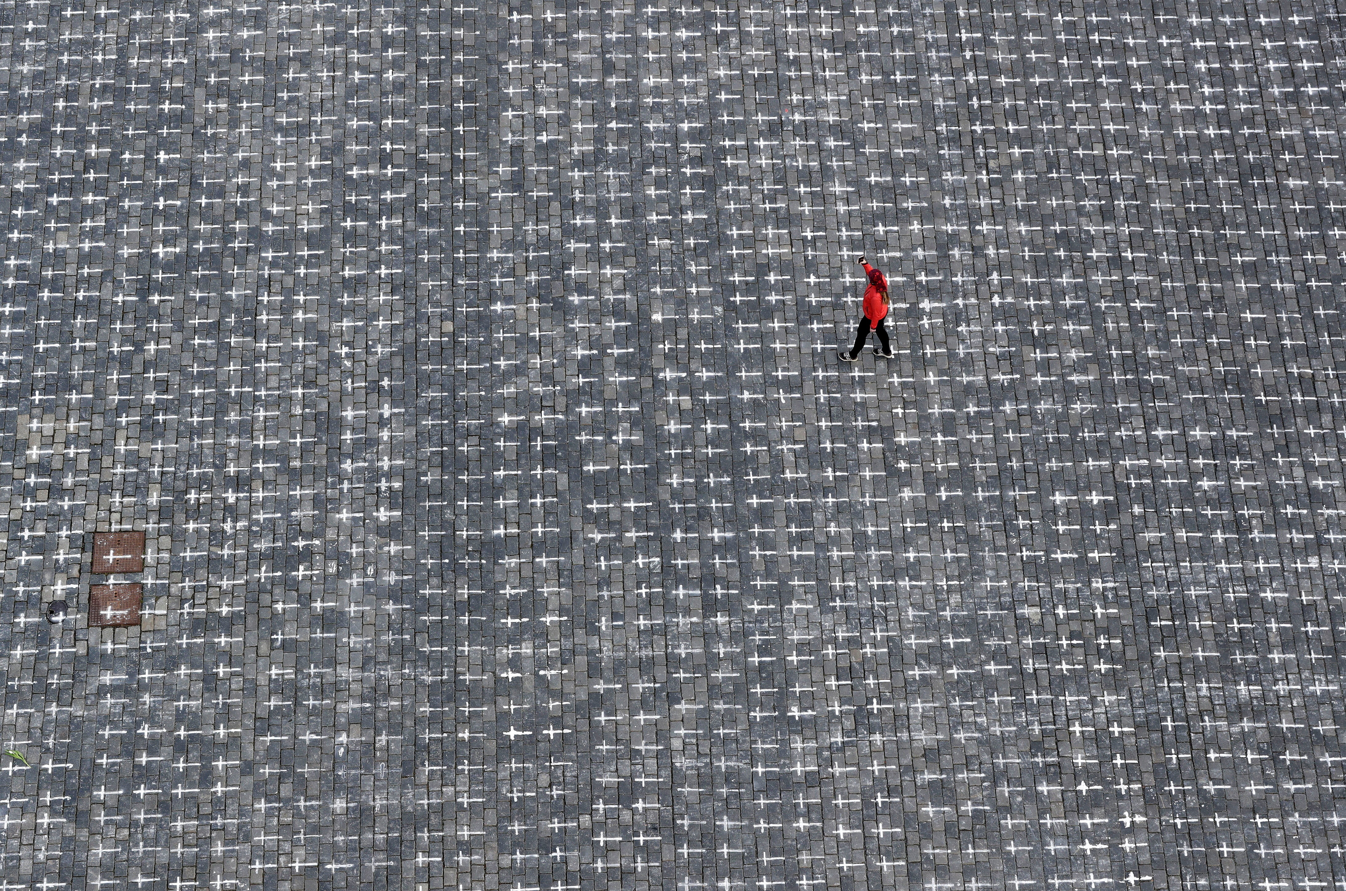 A woman walks across the Old Town Square where thousands of crosses have been painted on a pavement to commemorate the first anniversary since the death of the first Czech coronavirus disease (COVID-19) patient in Prague, Czech Republic, March 22, 2021.  REUTERS/David W Cerny - RC2EGM9VM614
