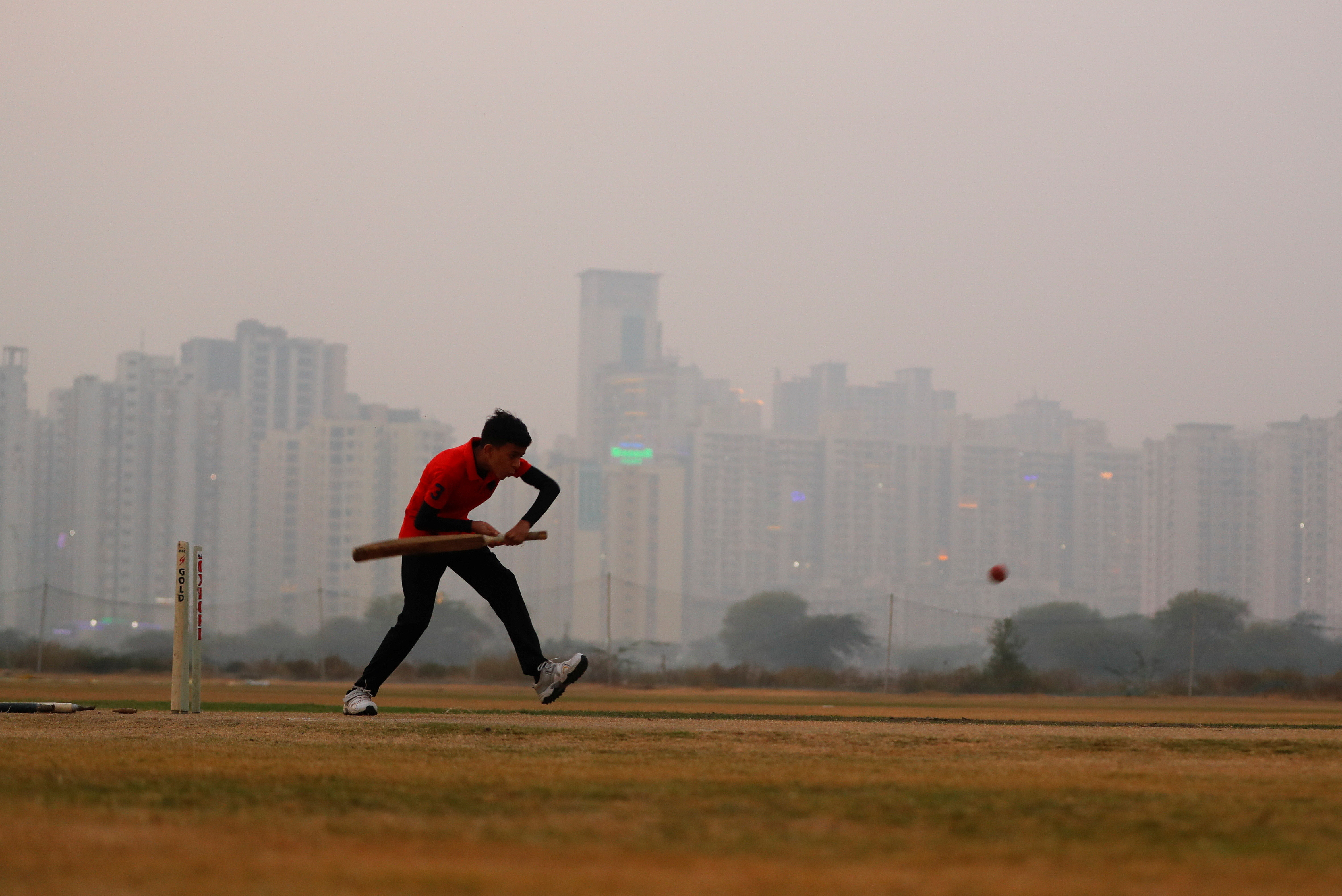 A boy plays cricket amidst smog at a playground in Noida on the outskirts of New Delhi, India, November 14, 2020.
