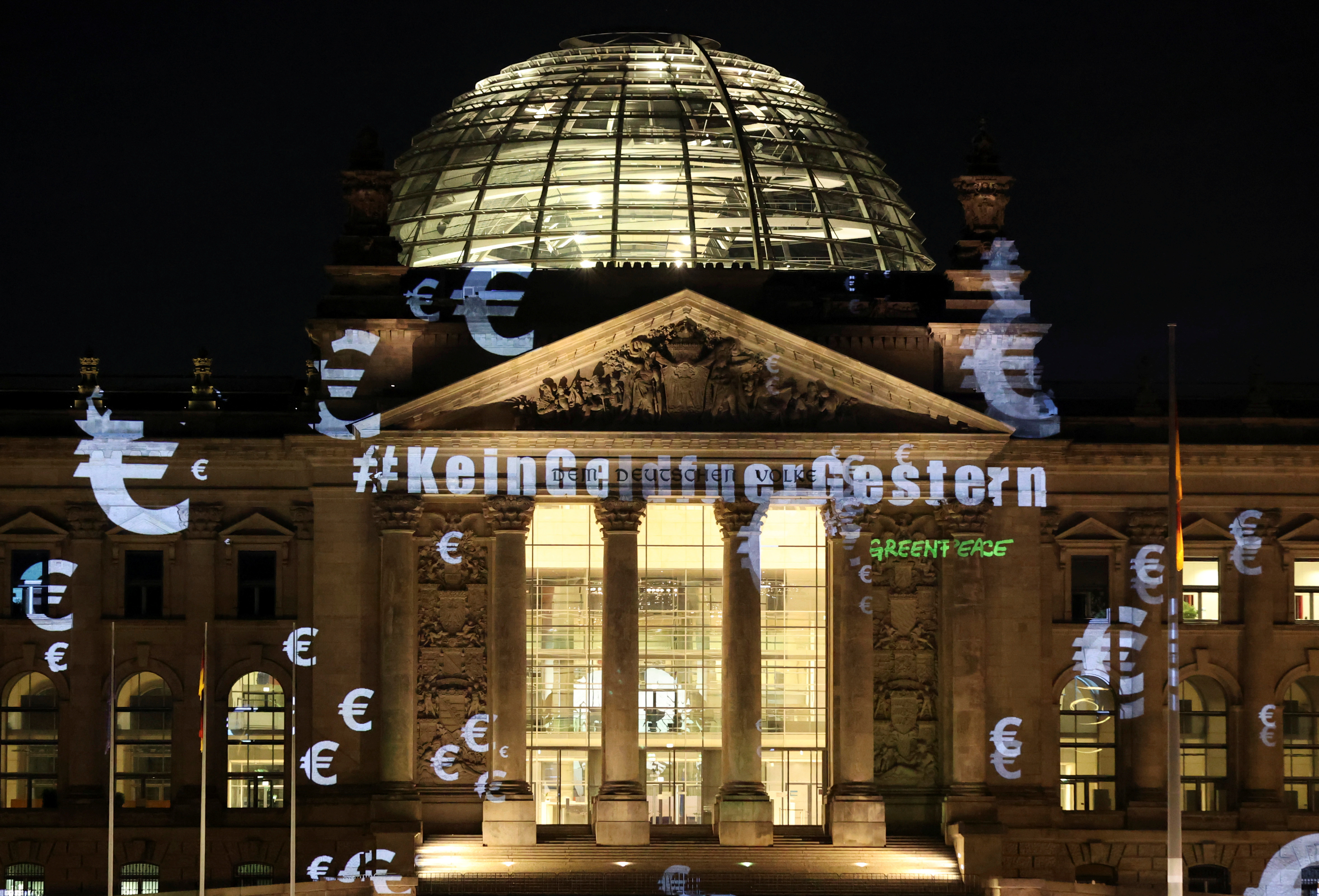 "Greenpeace activists project a slogan that reads ""No money for yesterday"" on the Reichstag building, June 3, 2020."