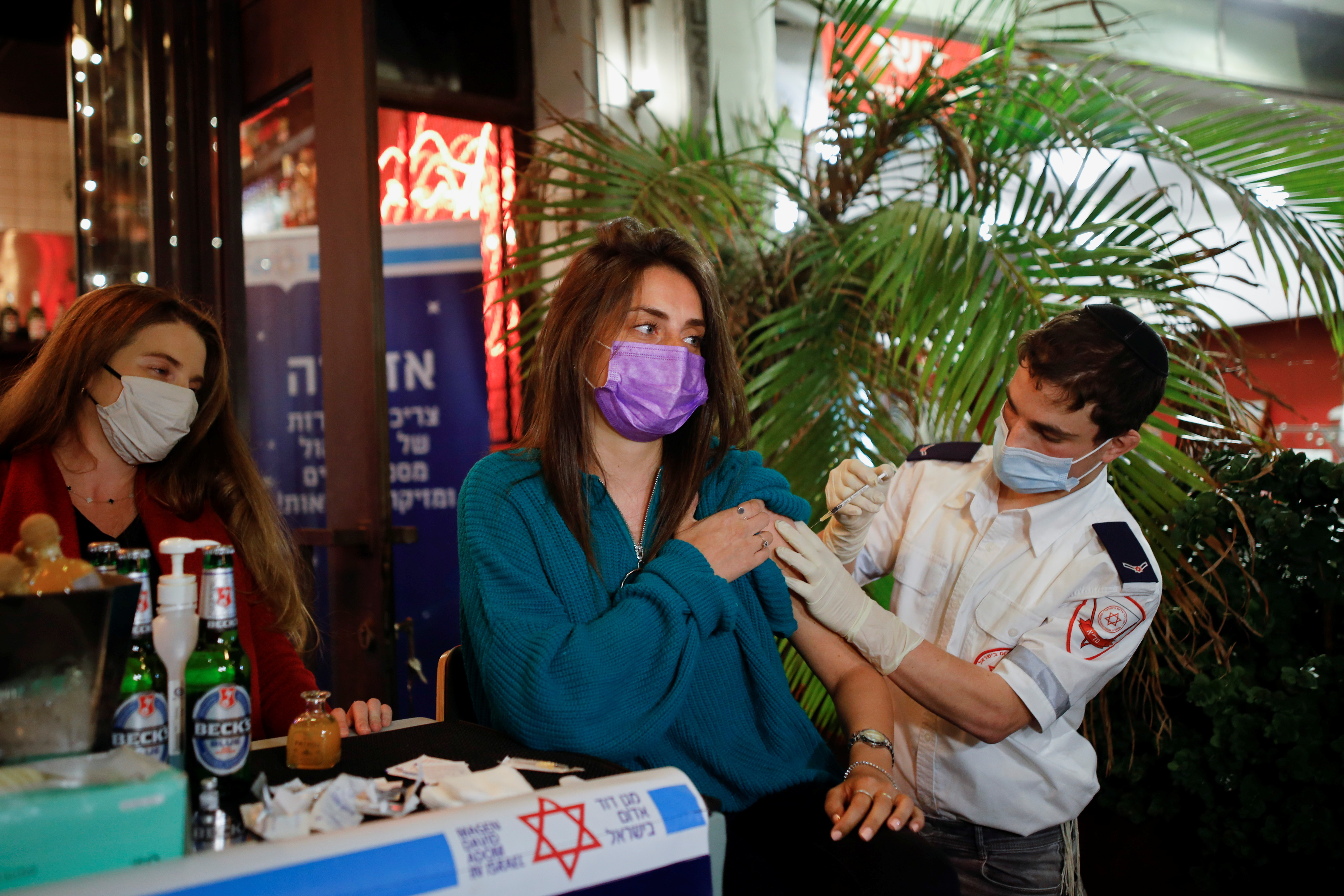 A woman receives a vaccination against the coronavirus disease (COVID-19) as part of a Tel Aviv municipality initiative offering a free drink at a bar to residents getting the shot, in Tel Aviv, Israel February 18, 2021. REUTERS/Corinna Kern - RC26VL9AZFSZ