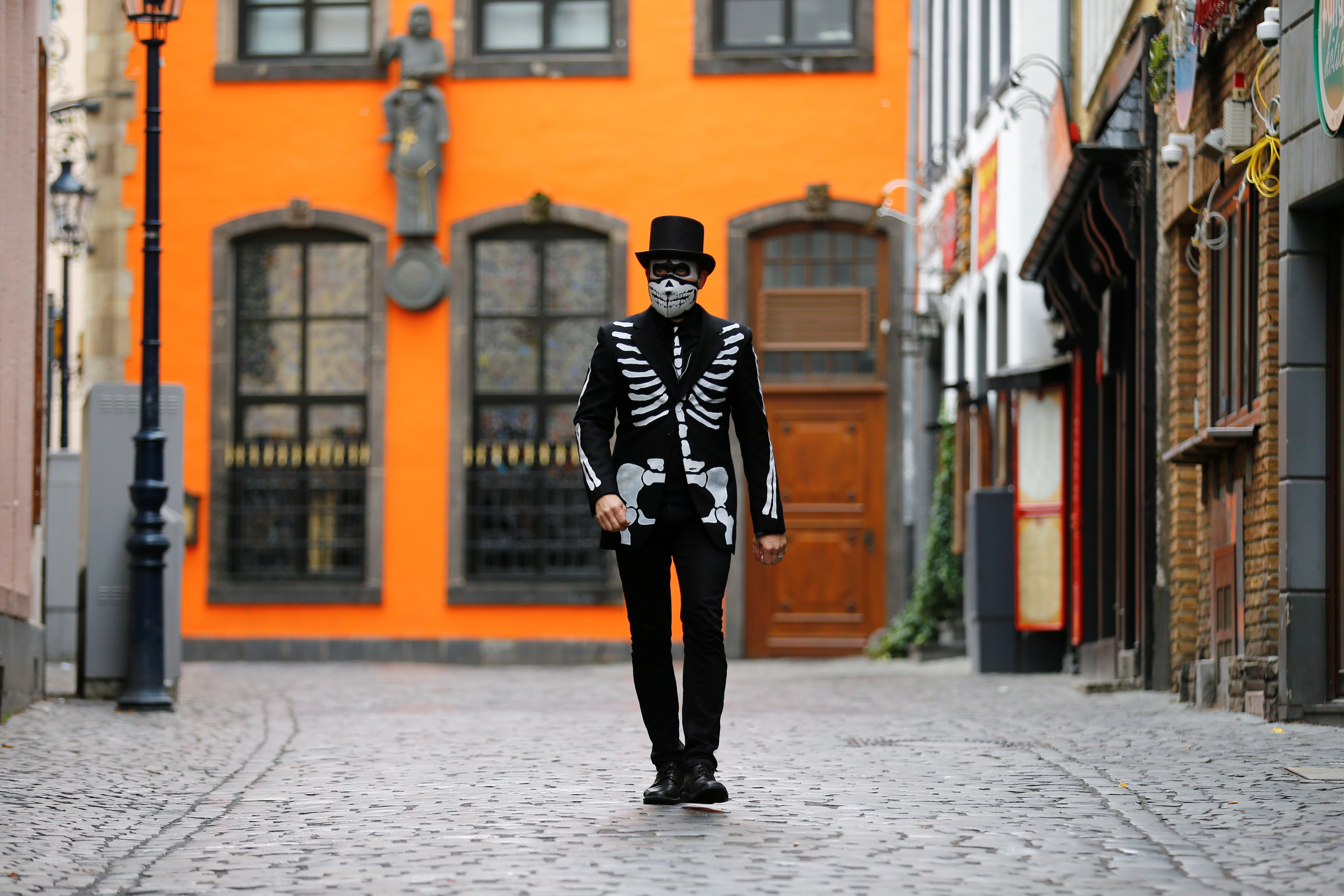"A lonely carnival reveller dressed as ""The Death"" walks through an empty street as the traditional celebrations for the start of the famous Cologne carnival season are officially cancelled due to the spread of the coronavirus disease (COVID-19) in Cologne, Germany, November 11, 2020. REUTERS/Thilo Schmuelgen - RC2Z0K9WZTZB"