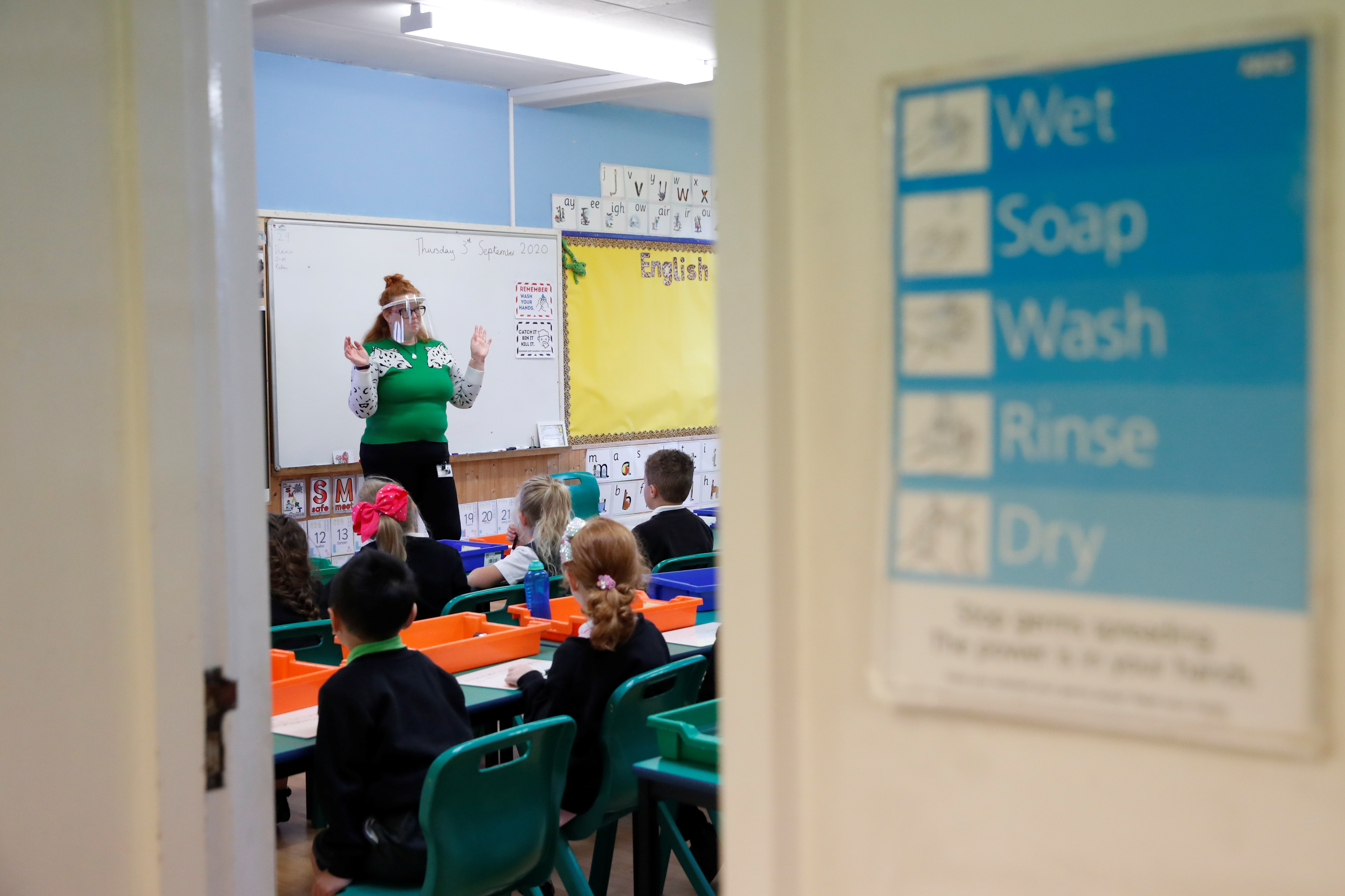 A hand washing advice is seen as a teacher wears a face shield on the first day of school at Holne Chase Primary School, amid the outbreak of the coronavirus disease (COVID-19), in Milton Keynes, Britain September 3, 2020. REUTERS/Andrew Boyers - RC20RI9B9KYB