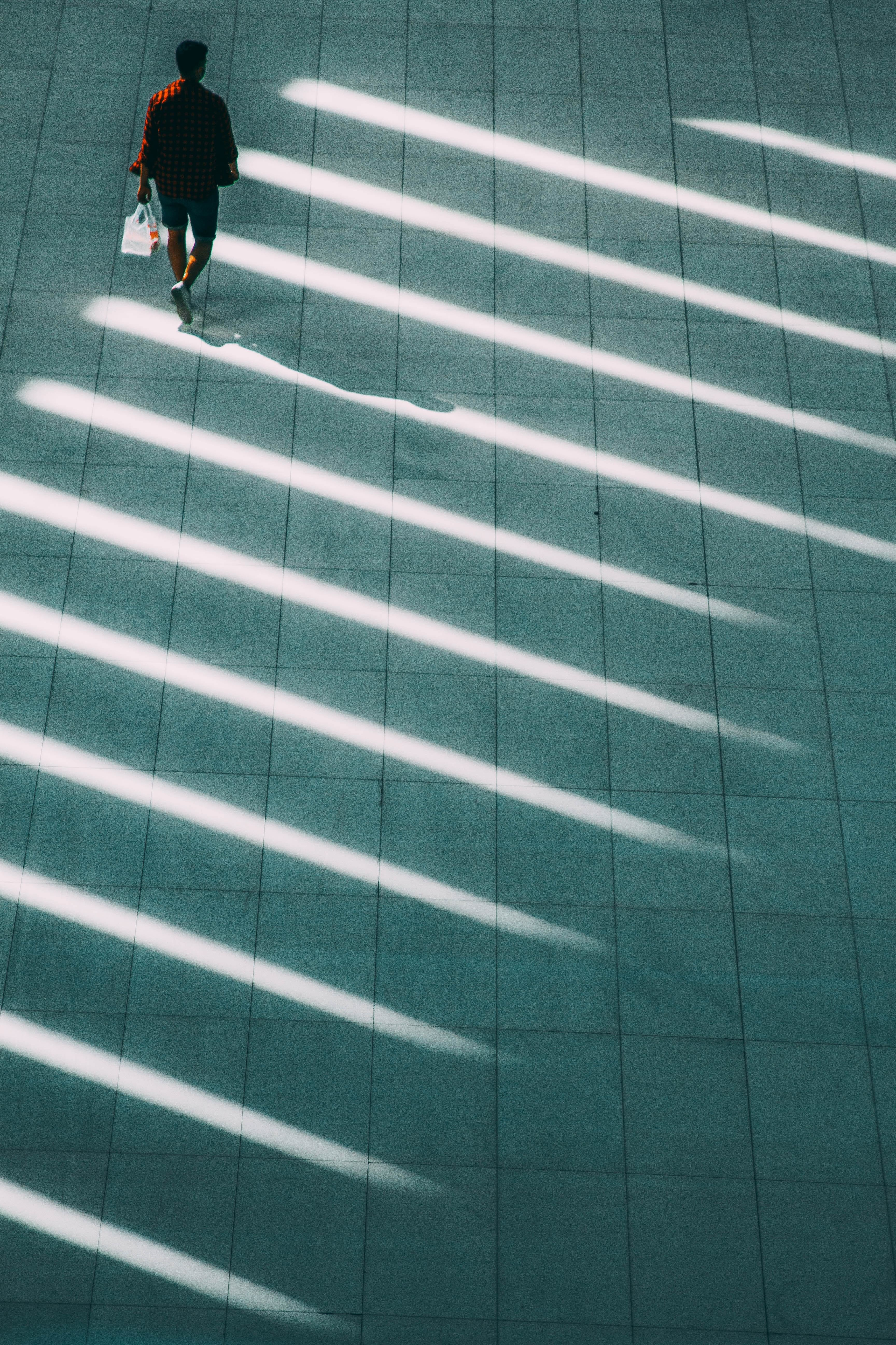 Man walking with shafts of sunlight at the World Trade Center - highlighting how the new global trade map is shifting from fixed capital to human capital
