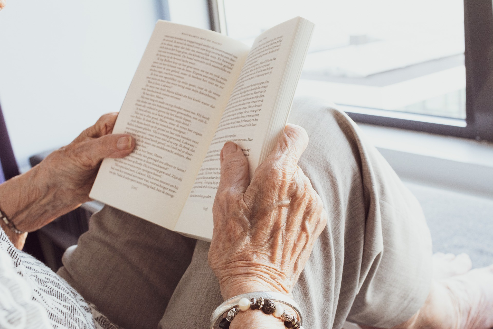 staying mentally engaged, like this older person here who is reading a book, is one of the Okinawan tips for a long life