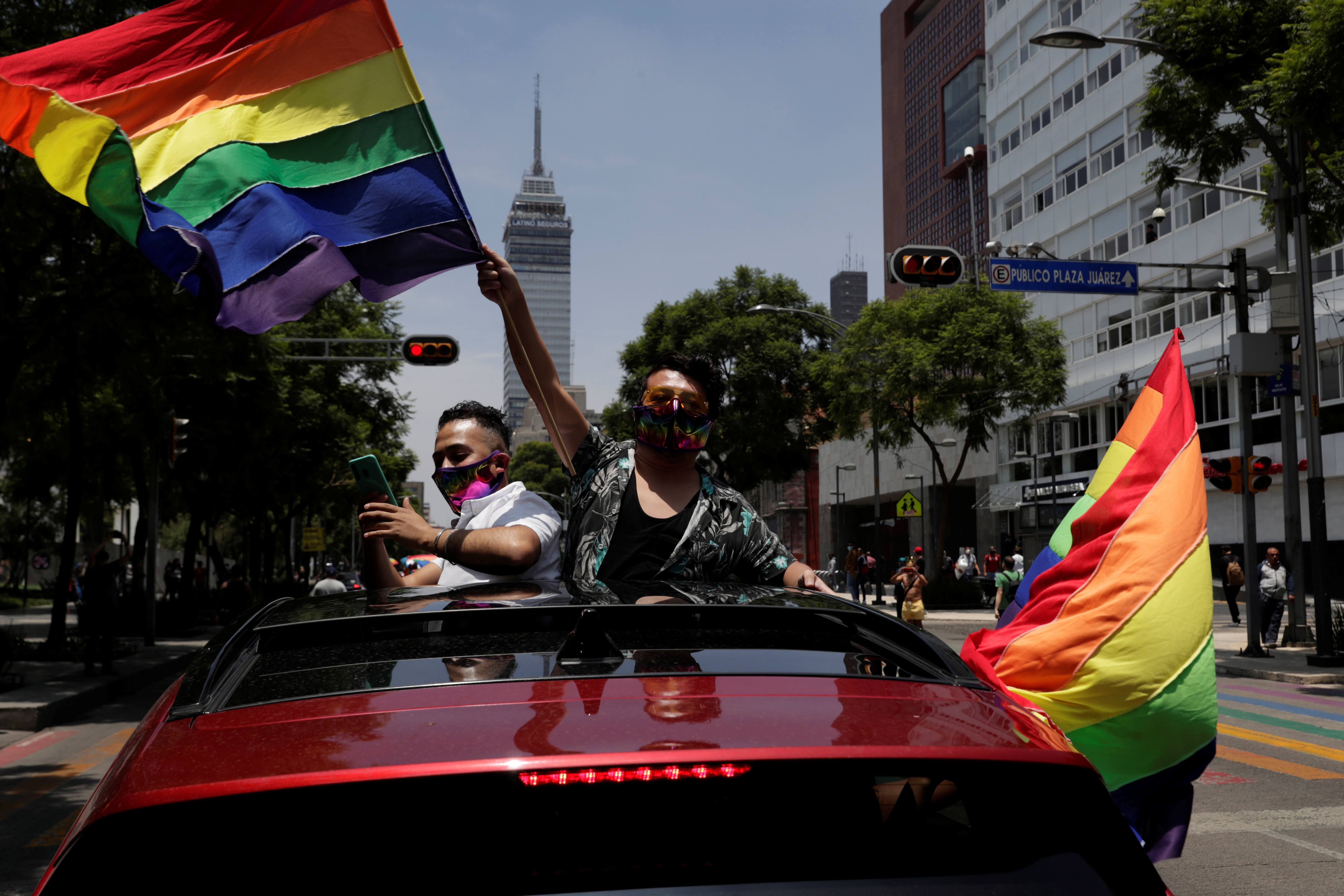 A participant flutters a rainbow flag near the Bellas Artes Palace to celebrate gay pride, although the Mexican LGBT community called for an online celebration as a protective measure amid the coronavirus disease (COVID-19) outbreak, in Mexico City, Mexico June 27, 2020 REUTERS/Henry Romero - RC20IH94V3C2