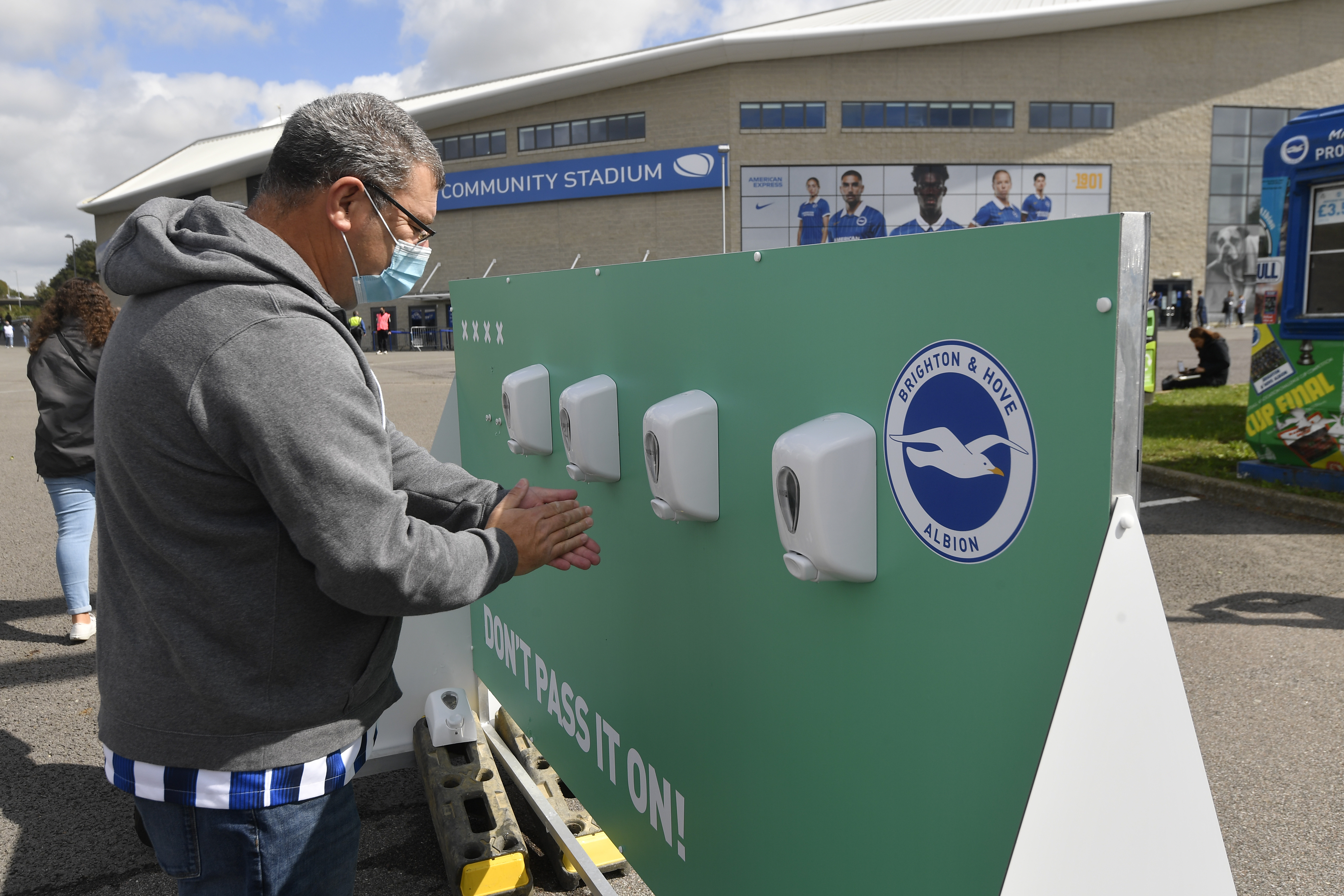 Soccer Football - Pre Season Friendly - Brighton & Hove Albion v Chelsea - The American Express Community Stadium, Brighton, Britain - August 29, 2020  A fan wearing a mask uses a hand sanitiser station outside the stadium before the match, as fans are allowed into a stadium following the outbreak of the coronavirus disease (COVID-19)