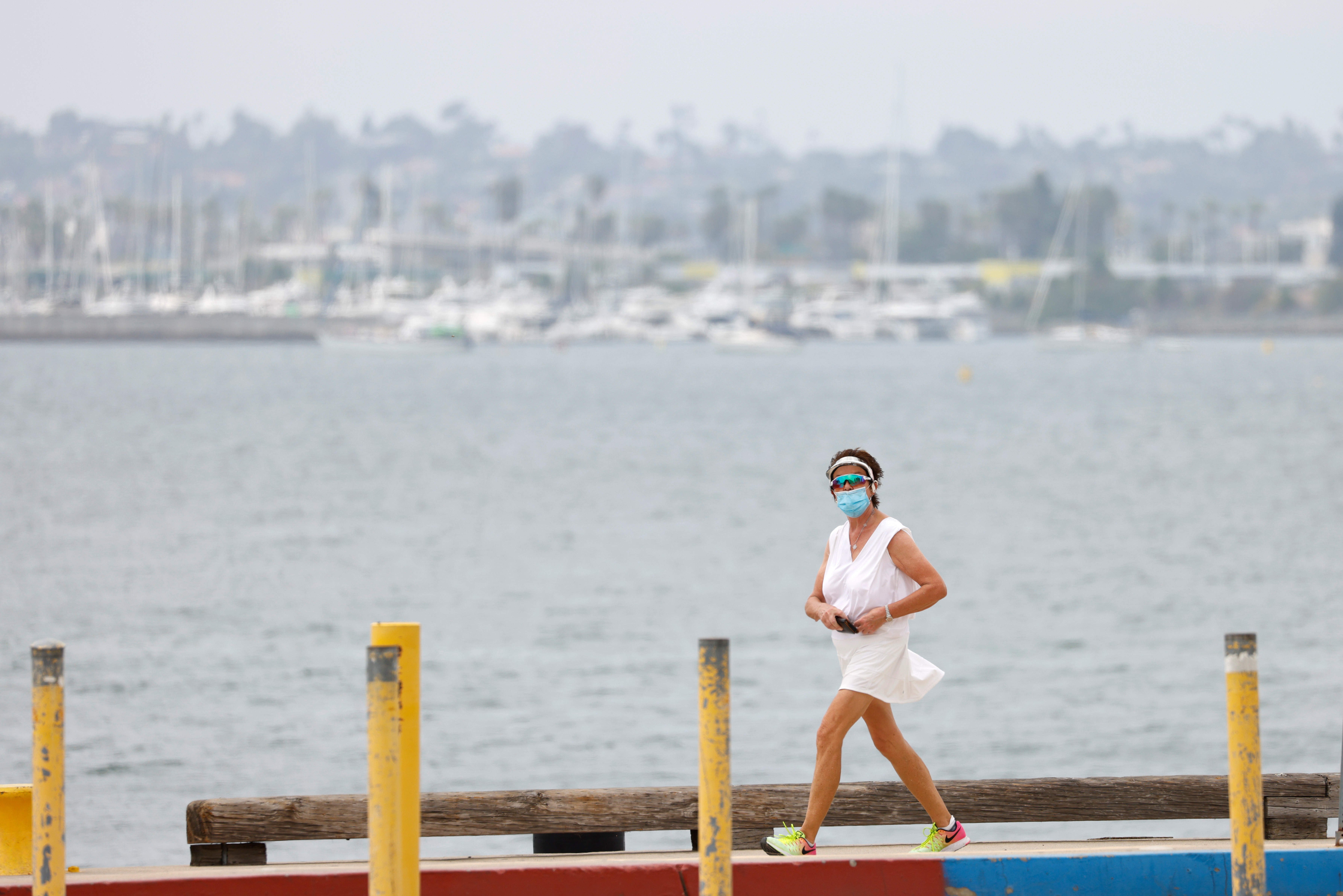 A woman wearing a protective mask takes a walk along the ocean amid a heatwave during the outbreak of the coronavirus disease (COVID-19) in San Diego, California, U.S., August 18, 2020. REUTERS/Mike Blake - RC2LGI9DY38P