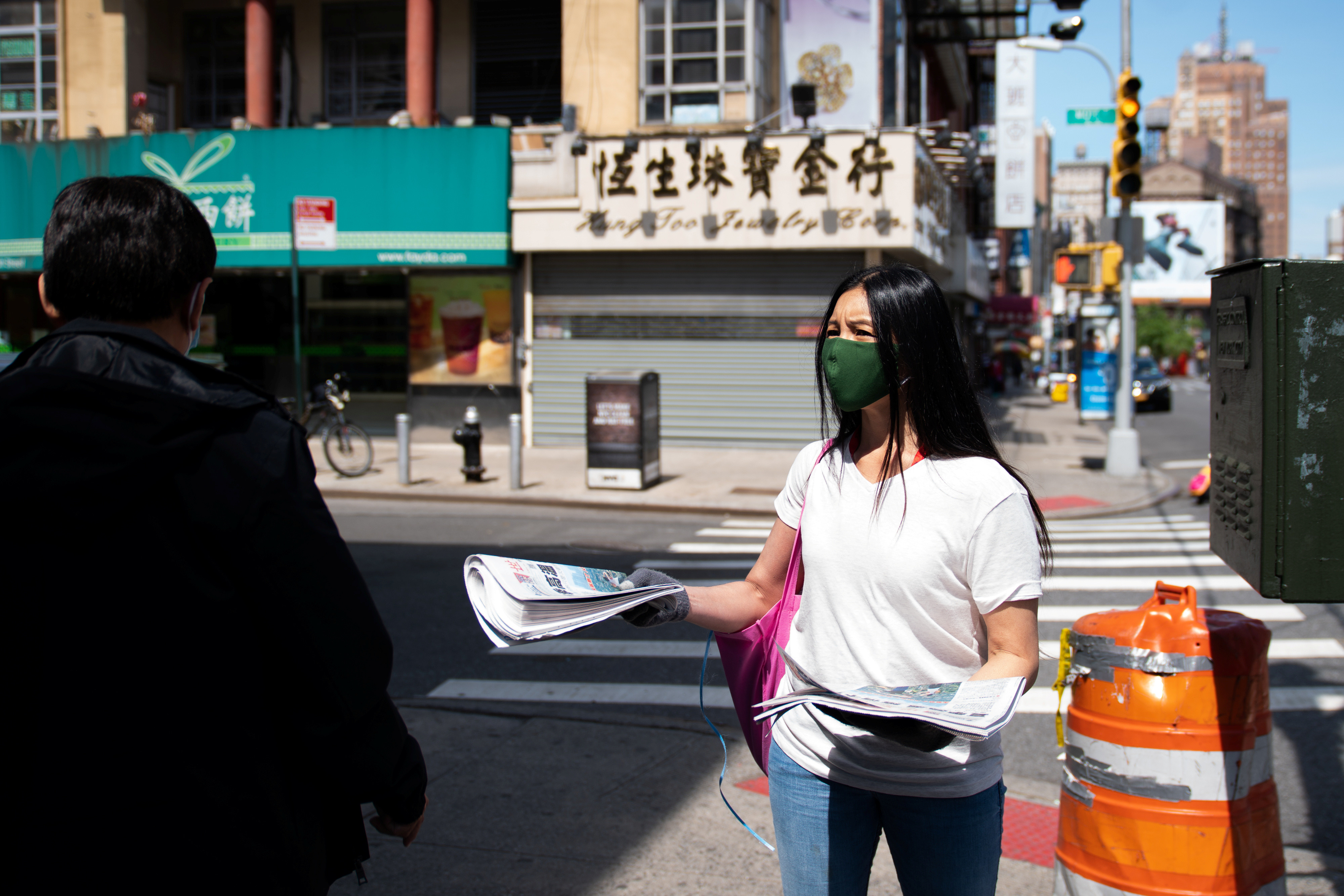 Shirley Ng, a volunteer for the Chinatown Block Watch neighborhood patrol group, distributes newspaper in Chinatown during the outbreak of the coronavirus disease (COVID-19) in New York City, New York, U.S., May 17, 2020. Picture taken May 17,2020. REUTERS/Jeenah Moon - RC2BYG9N432A