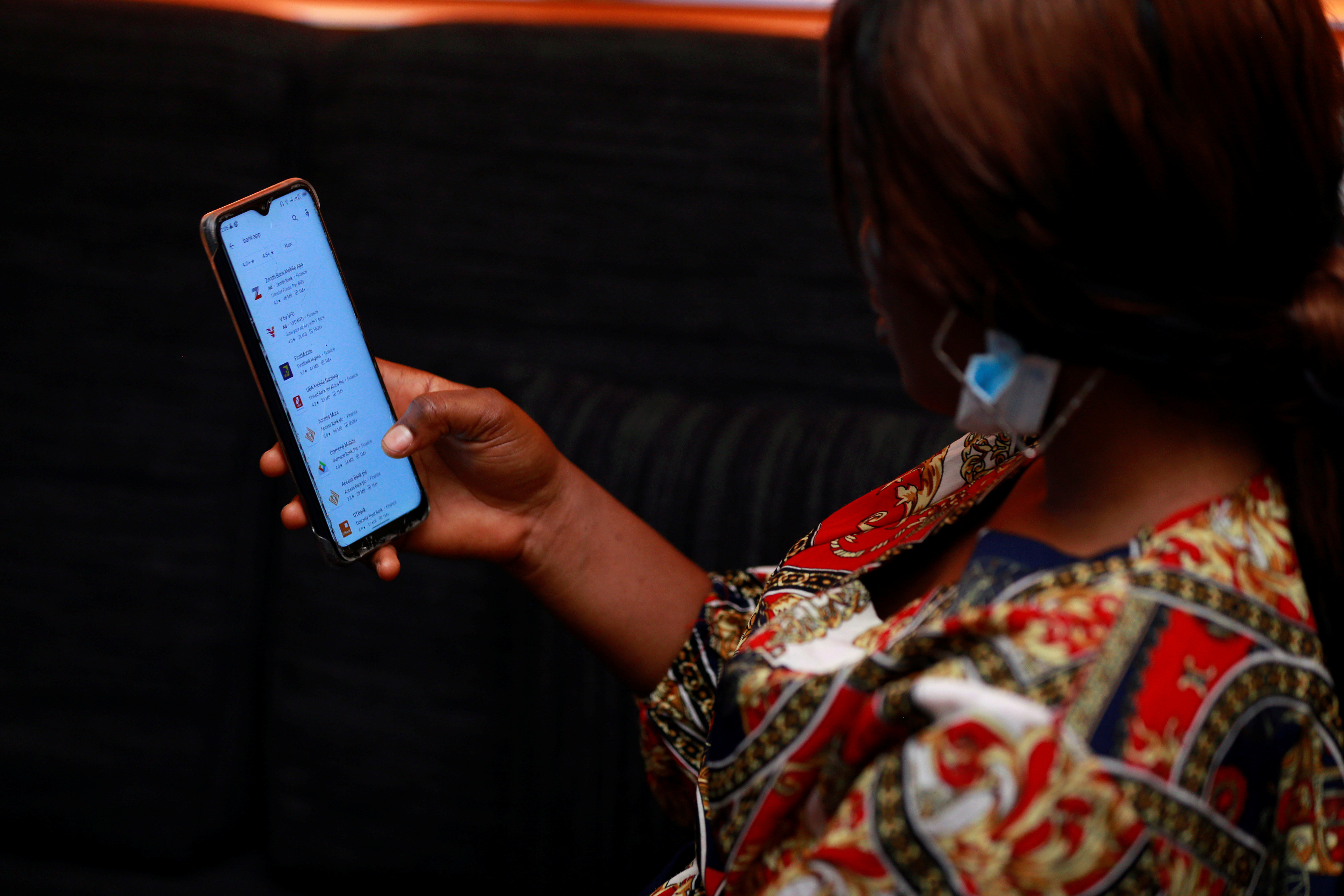 A woman looks at Nigerian banks apps on a smart phone in Abuja, Nigeria.