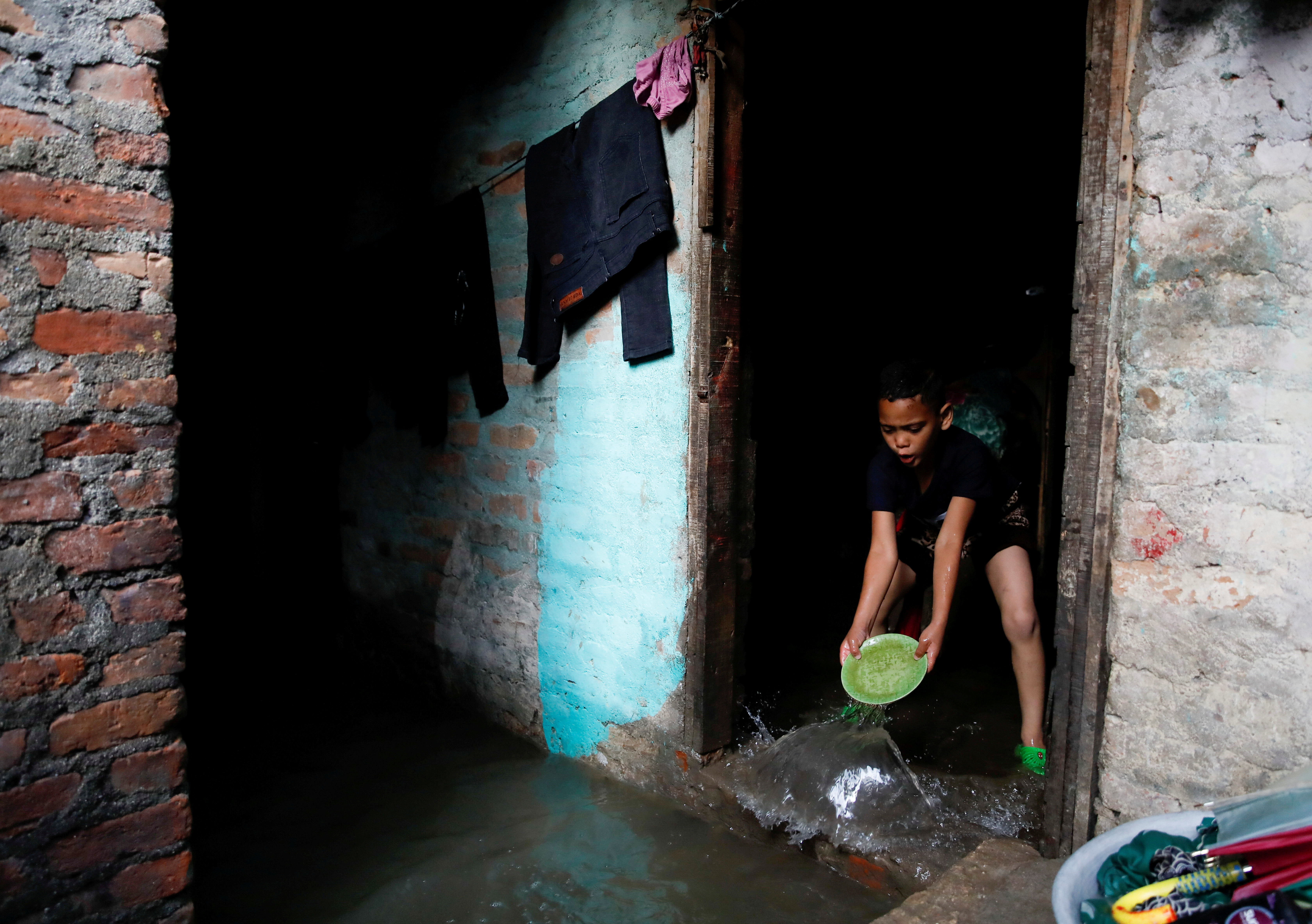 A boy uses a plate to clear water entering his house as the river overflows due to incessant rainfall at a slum along the bank of Bagmati River in Kathmandu, Nepal July 20, 2020. REUTERS/Navesh Chitrakar     TPX IMAGES OF THE DAY - RC22XH9UEVBB