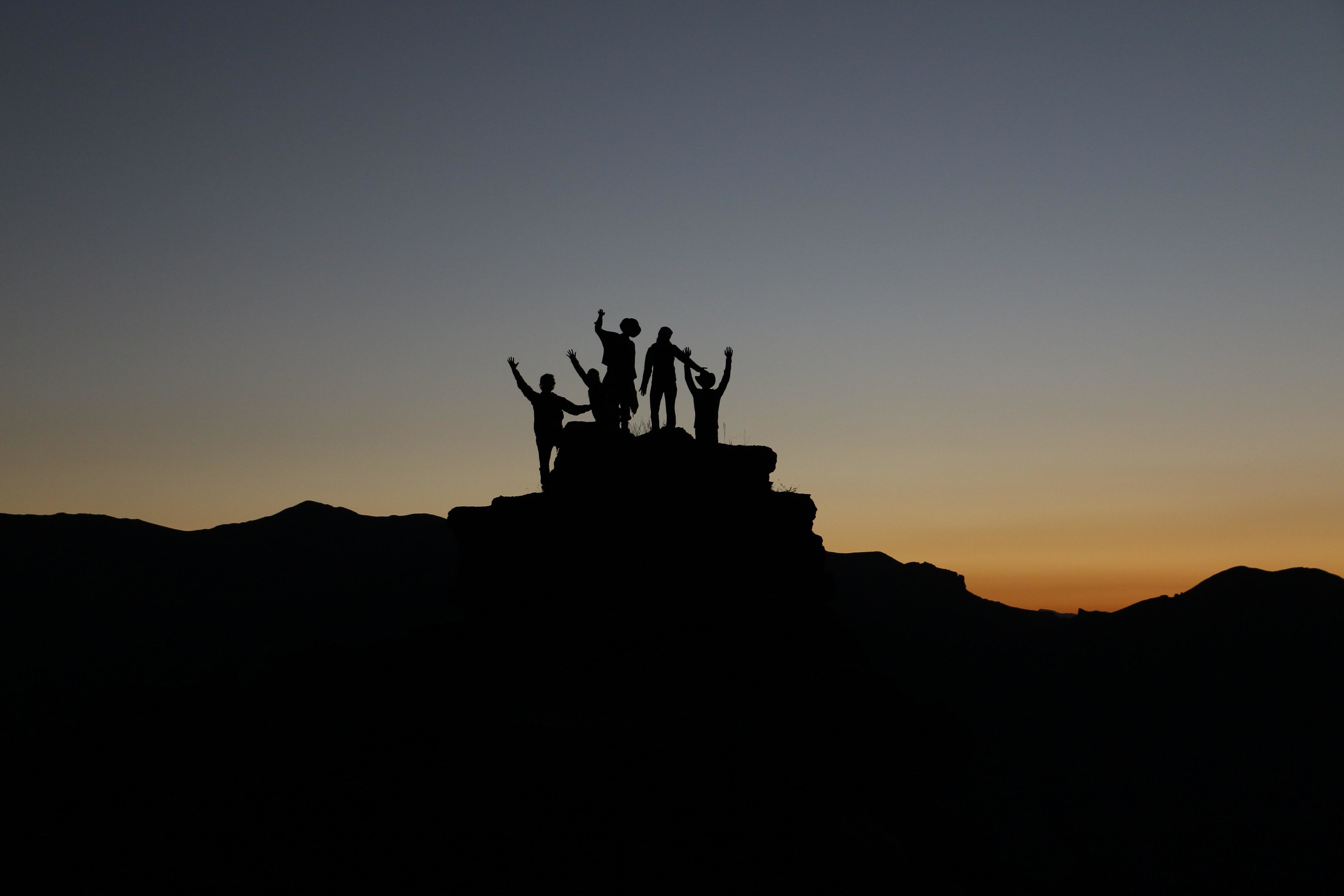 group of people climb to the top of a mountain and raise their hands in the air