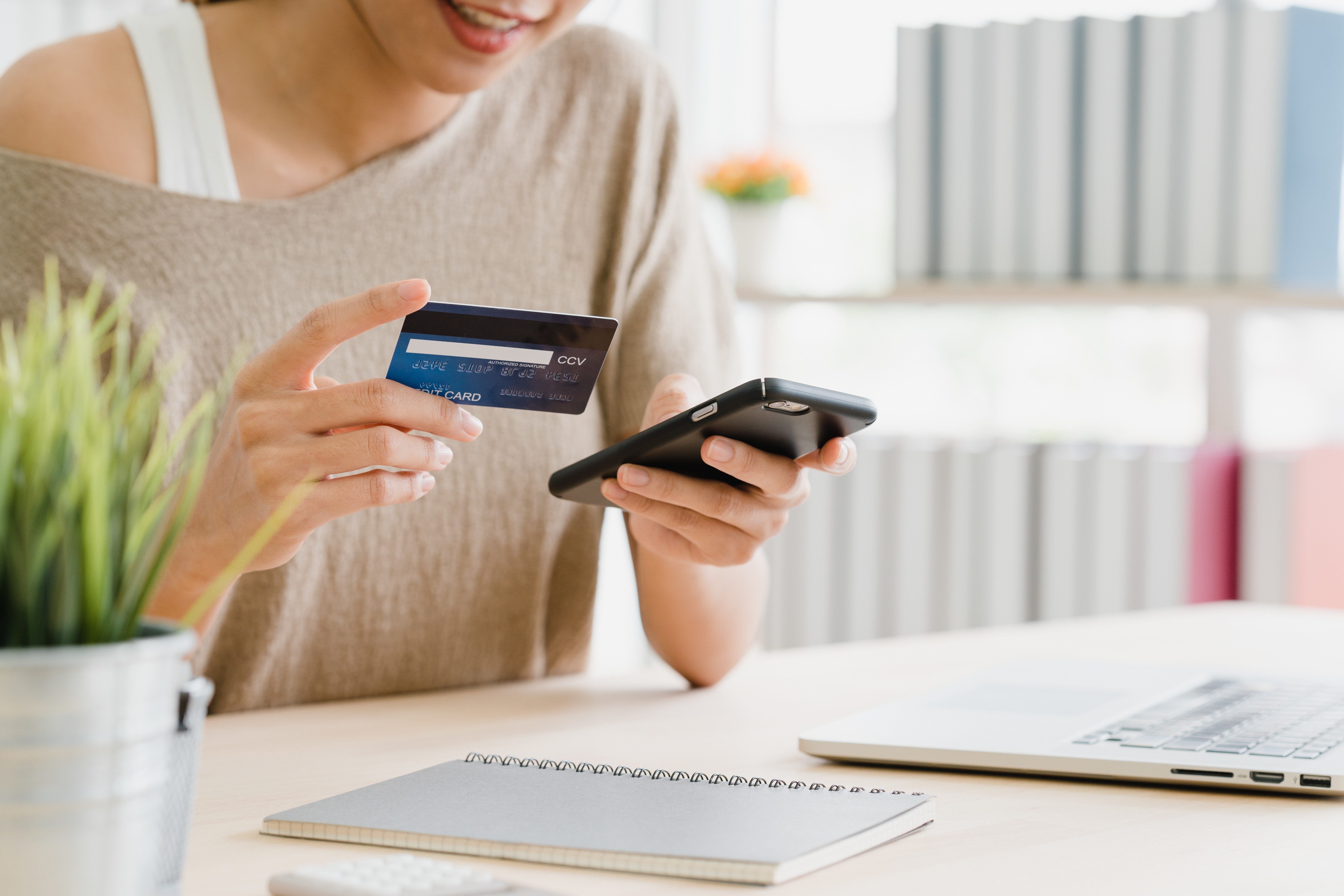 Woman using smartphone buying online shopping by credit card while wear sweater sitting on desk in living room at home.