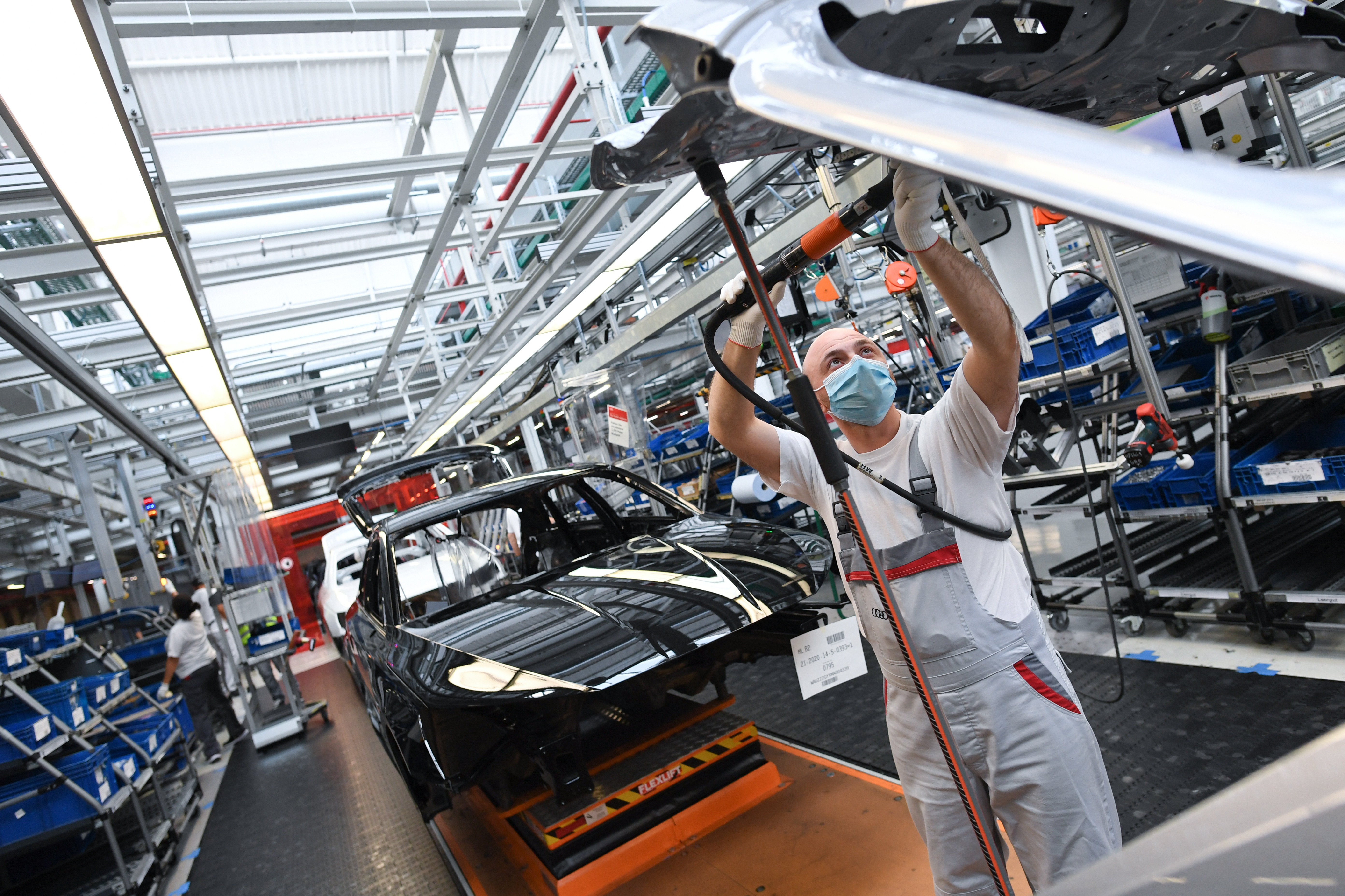 An employee works at the A3 and A4 production line of the German car manufacturer Audi in Ingolstadt, Germany, June 3, 2020.