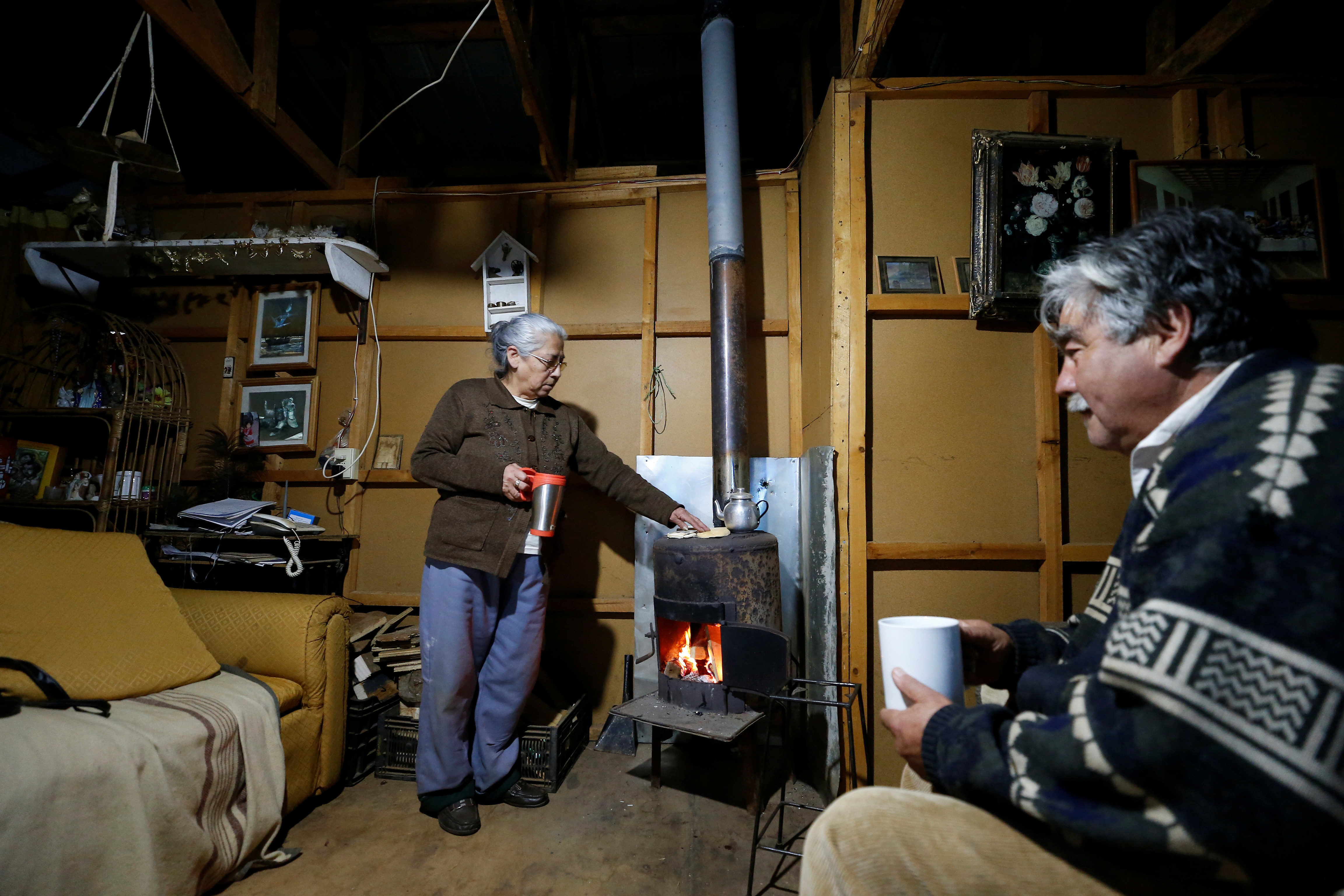 An elderly couple are seen by a wood burning stove in their home.