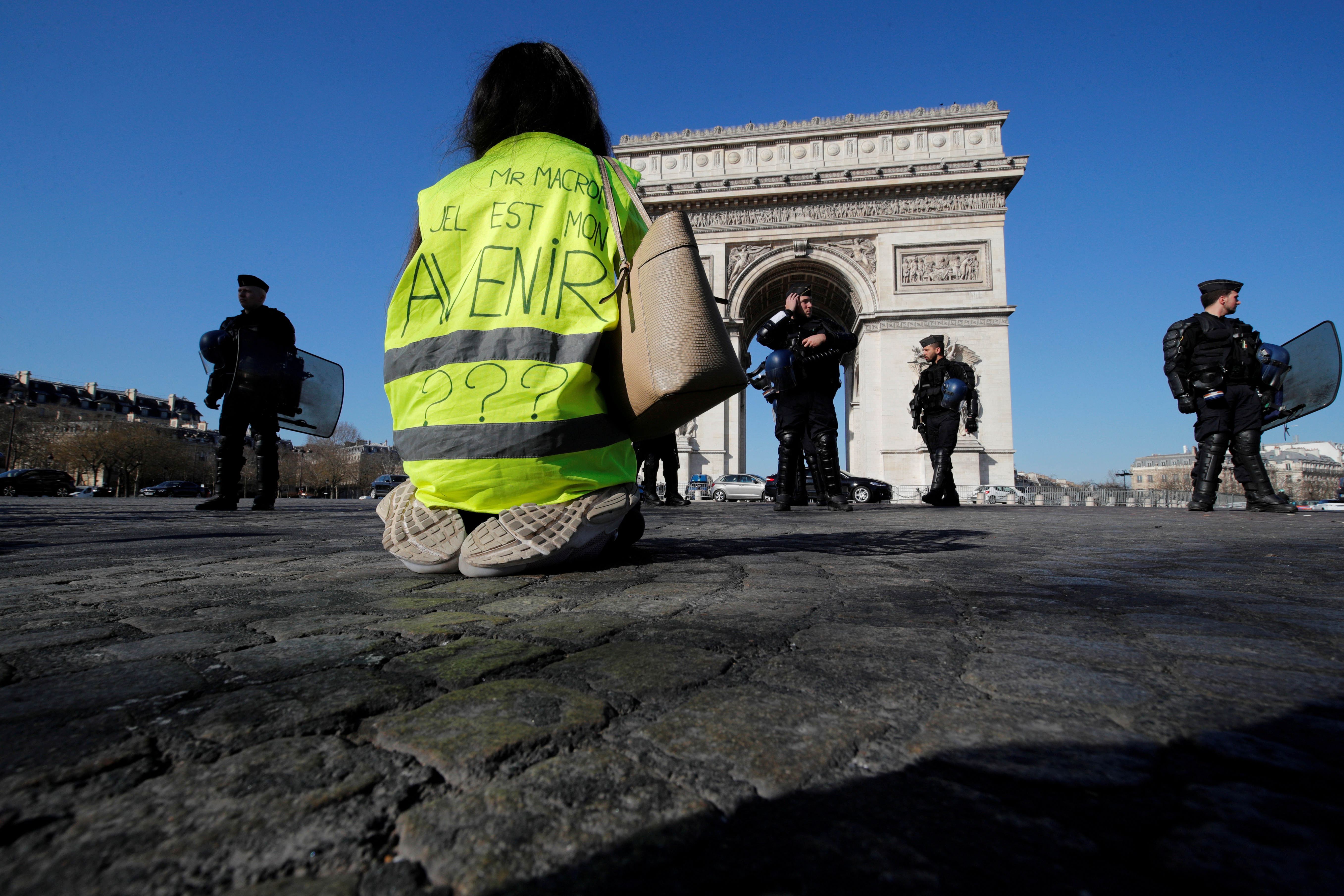 """A protester wearing a yellow vest kneels on the Champs Elysees near the Arc de Triomphe during a demonstration by the """"yellow vests"""" movement in Paris, France, February 23, 2019. Message reads, """"Mr Macron, What is my Future"""".  REUTERS/Philippe Wojazer     TPX IMAGES OF THE DAY - RC1A56F17E90"""