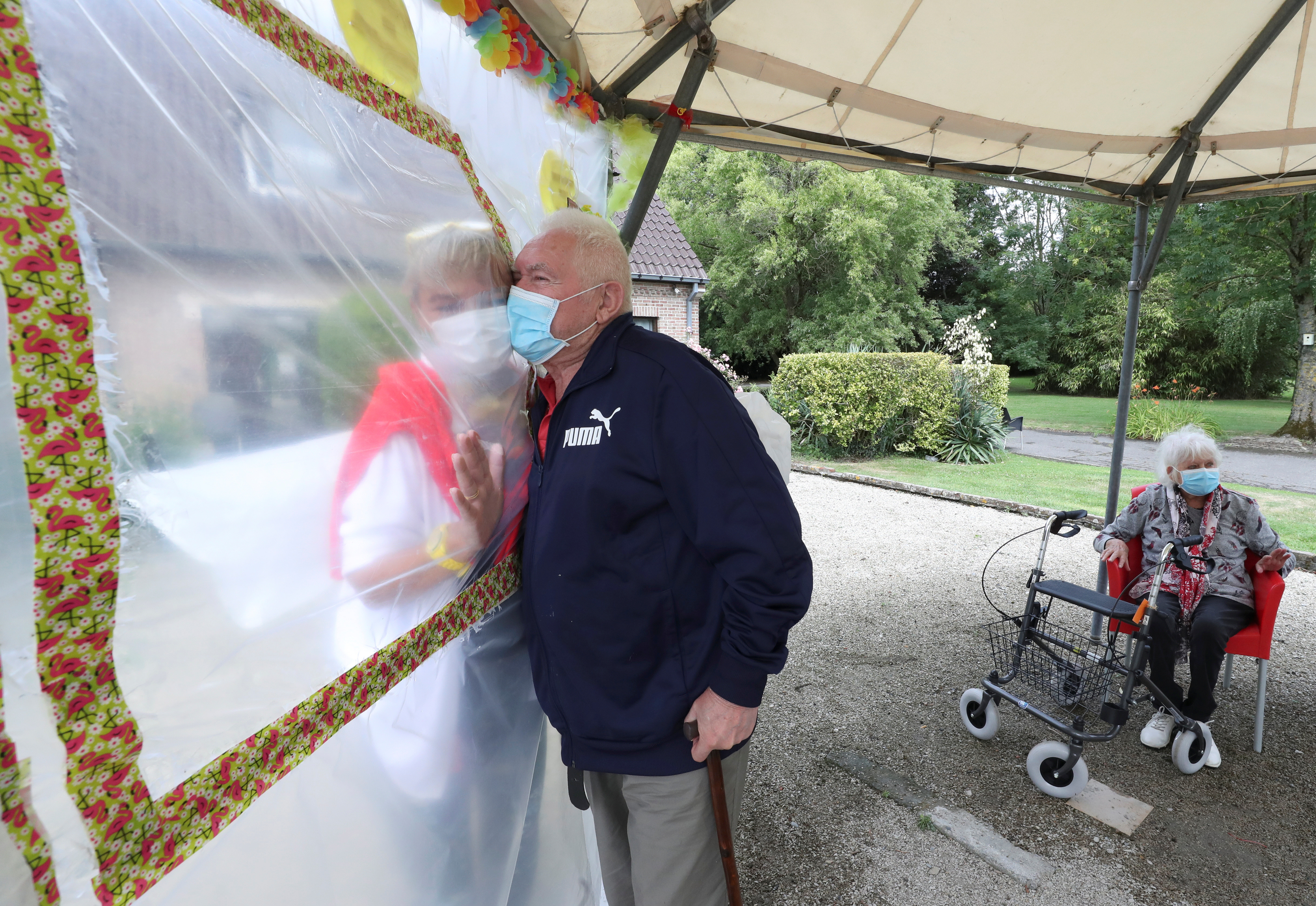 """Albert Letellier, 86, a resident at Belgian nursing home  """"Le Jardin de Picardie""""  enjoy hugs and cuddles with Marie-Christine Desoer, the director of the residence, through a wall made with plastic sheets to protect against potential coronavirus disease (COVID-19) infection, in Peruwelz, Belgium July 1, 2020. Picture taken July 1, 2020. REUTERS/Yves Herman - RC2ZKH9SWL2M"""