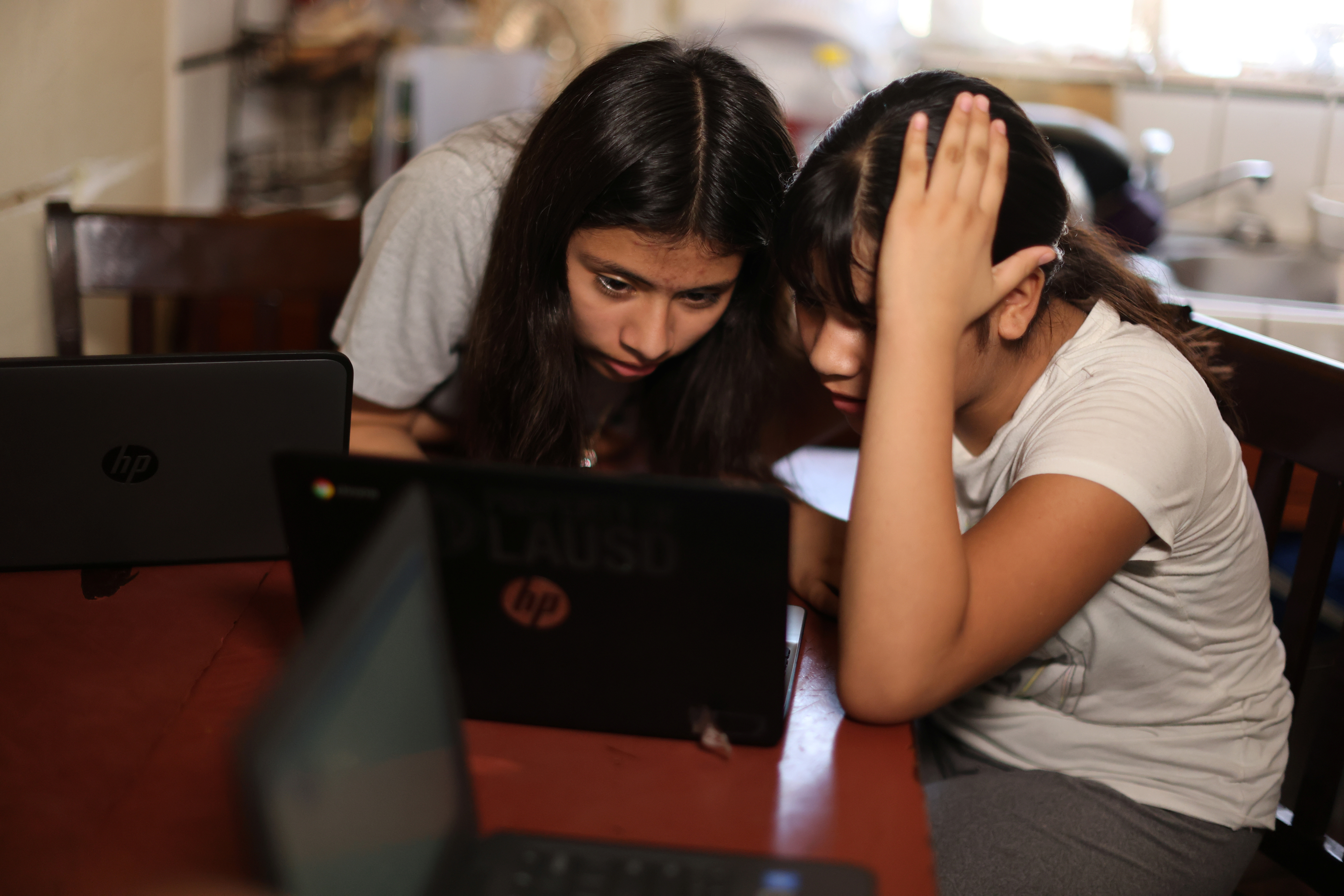 Los Angeles Unified School District (LAUSD) students Keiley Flores, 13, and Andrea Ramos, 10, work on school-issued computers with unreliable internet connectivity, at their home in Los Angeles, California, U.S., August 18, 2020.  REUTERS/Lucy Nicholson - RC2LGI9TPNZ9
