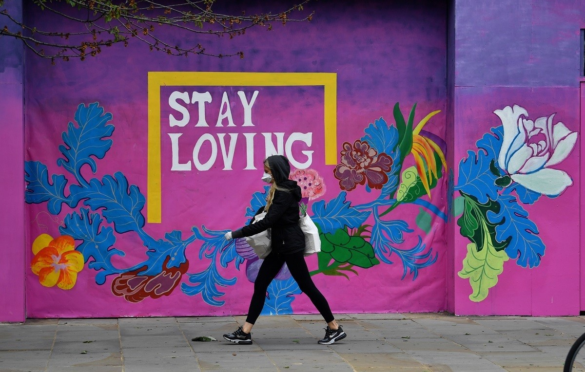 A woman wearing a protective face mask and gloves is seen walking past a mural, following the outbreak of the coronavirus disease (COVID-19), London, Britain, May 11, 2020. REUTERS/Dylan Martinez - RC2EMG9RRWMR