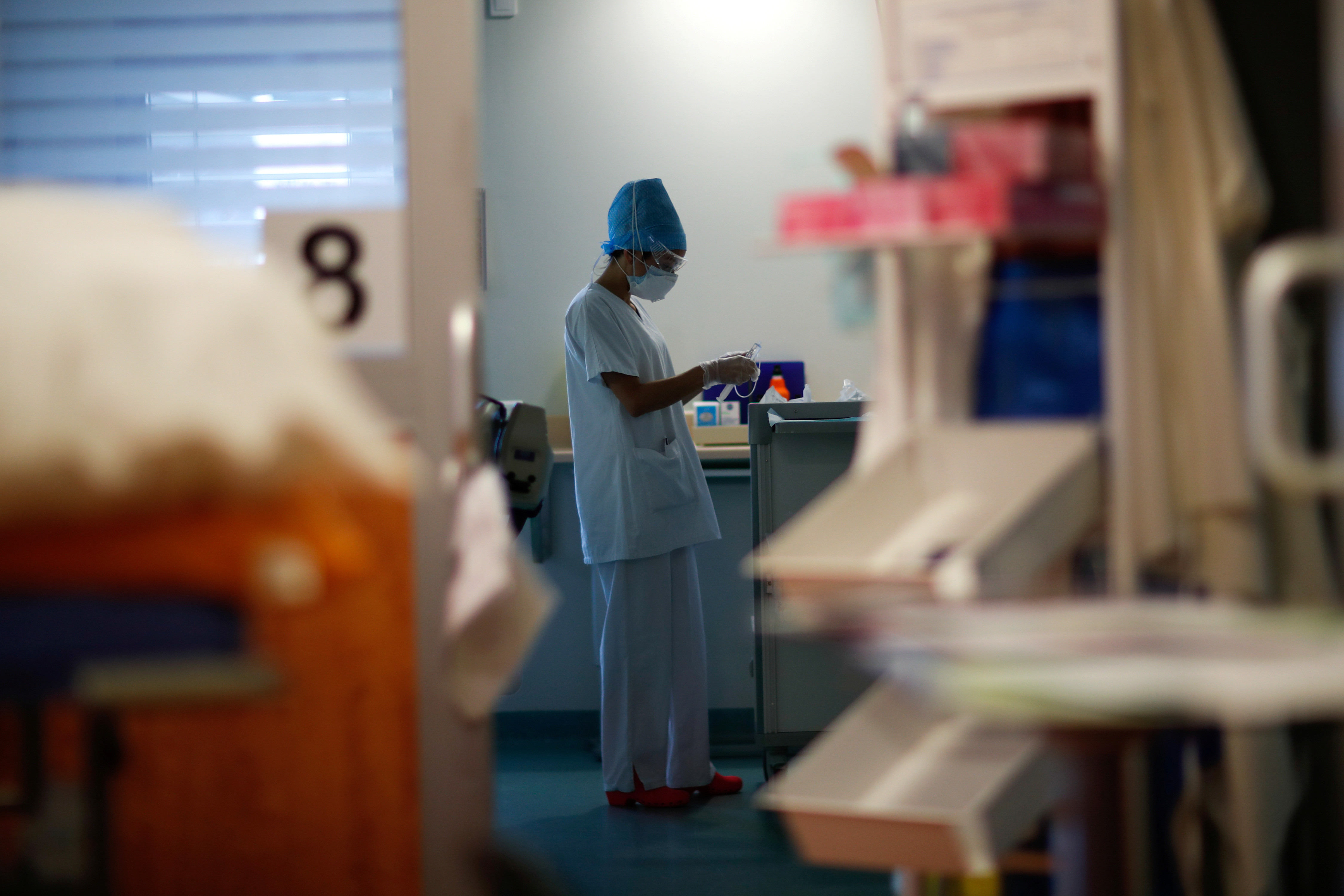 A medical staff member works in the Intensive Care Unit (ICU) for coronavirus disease (COVID-19) patients at the Robert Ballanger hospital in Aulnay-sous-Bois near Paris during the outbreak of the coronavirus disease in France, April 29, 2020. Seine-Saint-Denis, a mainly working class and multiracial suburb, was already lacking doctors and resources before the coronavirus crisis and has seen a bigger spike in mortality than neighbouring Paris. But despite being understaffed, teams at Robert Ballanger hospital reorganized to prioritize emergency health and have worked long hours, giving everything to fight the virus. Picture taken April 30, 2020. REUTERS/Gonzalo Fuentes - RC25JG94KZCV