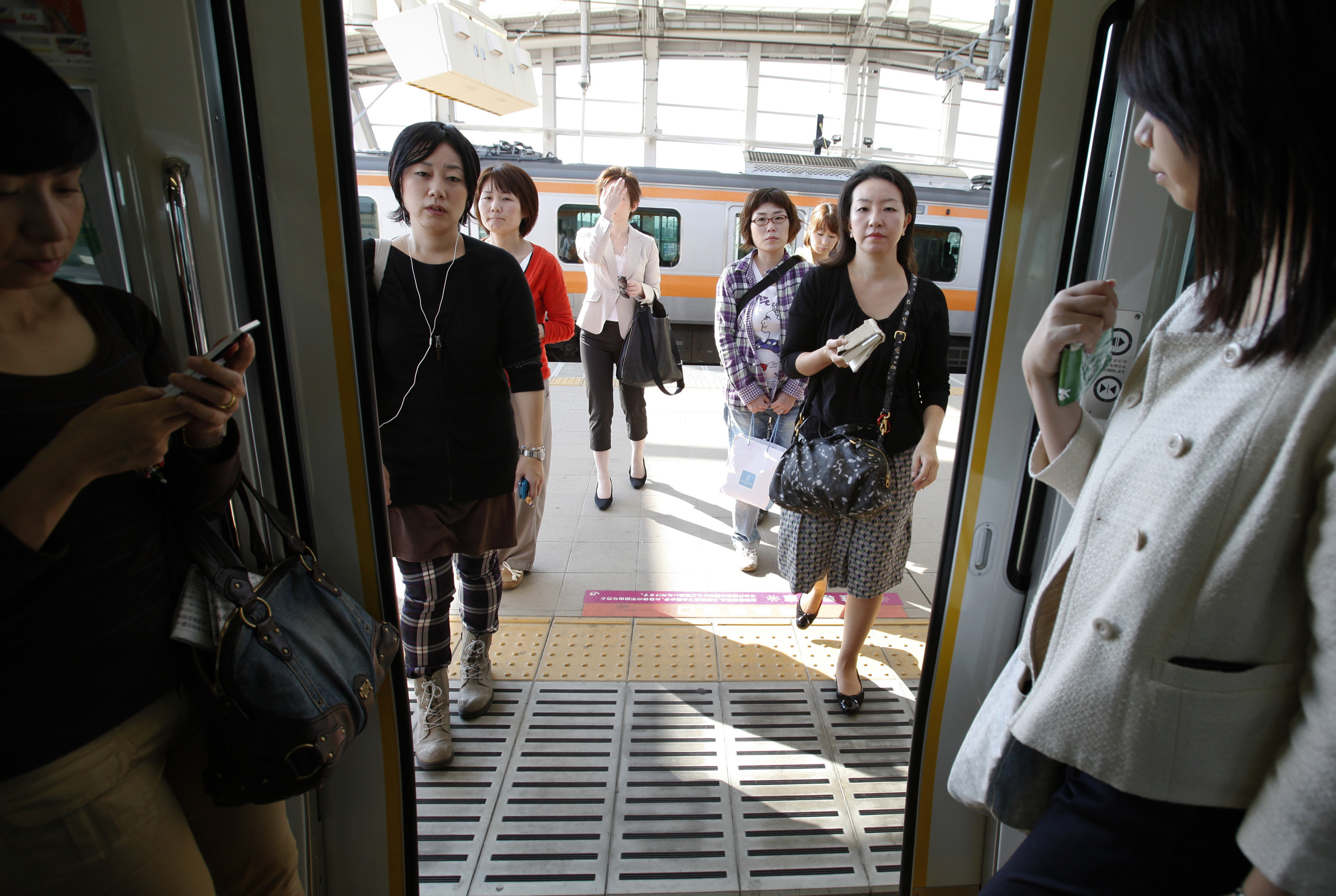 "Workers board a ""women-only"" passenger train during rush hour in Tokyo."