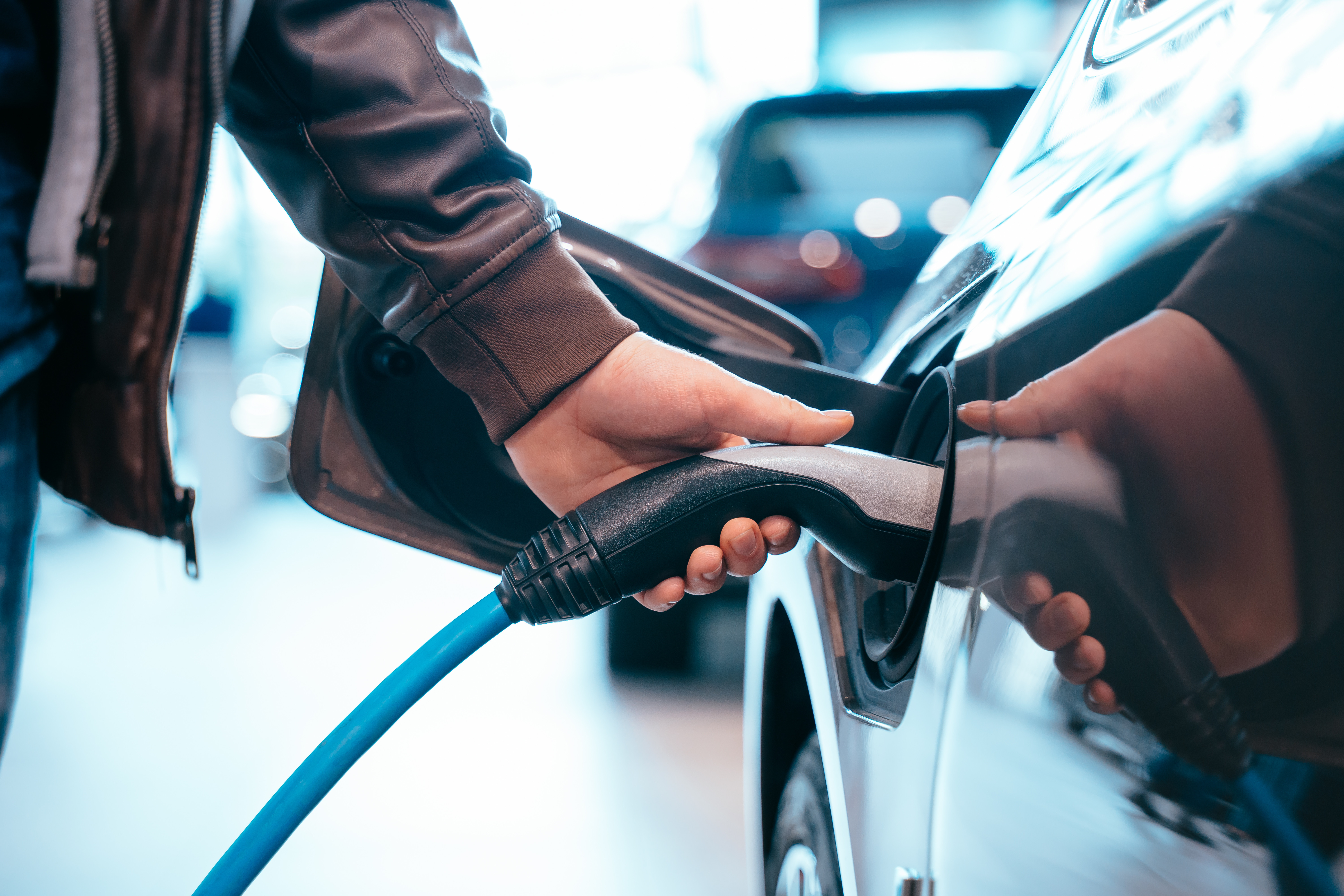Closes up Human hand is holding Electric Car Charging connect to Electric car