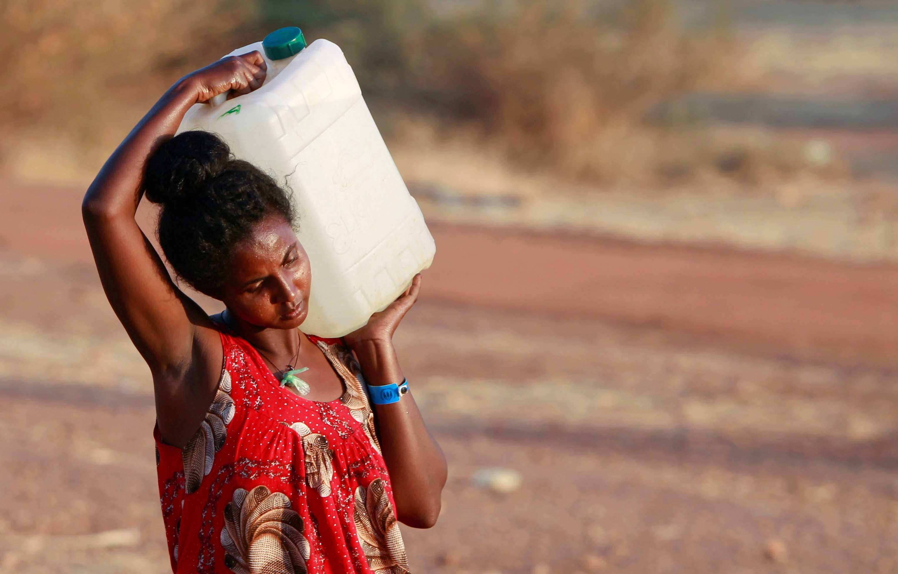 a woman carries a container of water