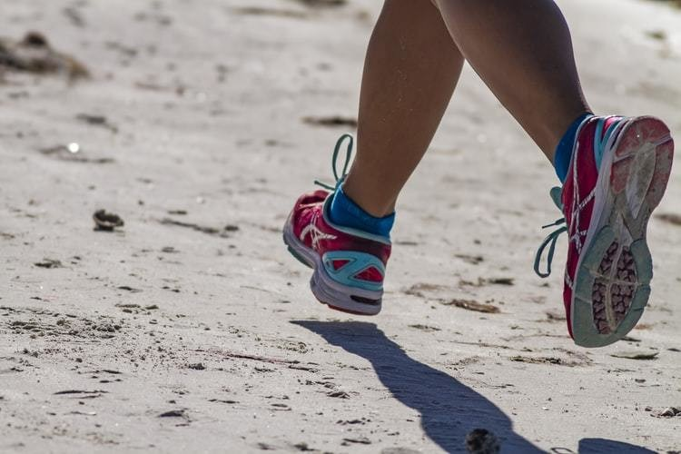 a close up of someone's trainers while they run