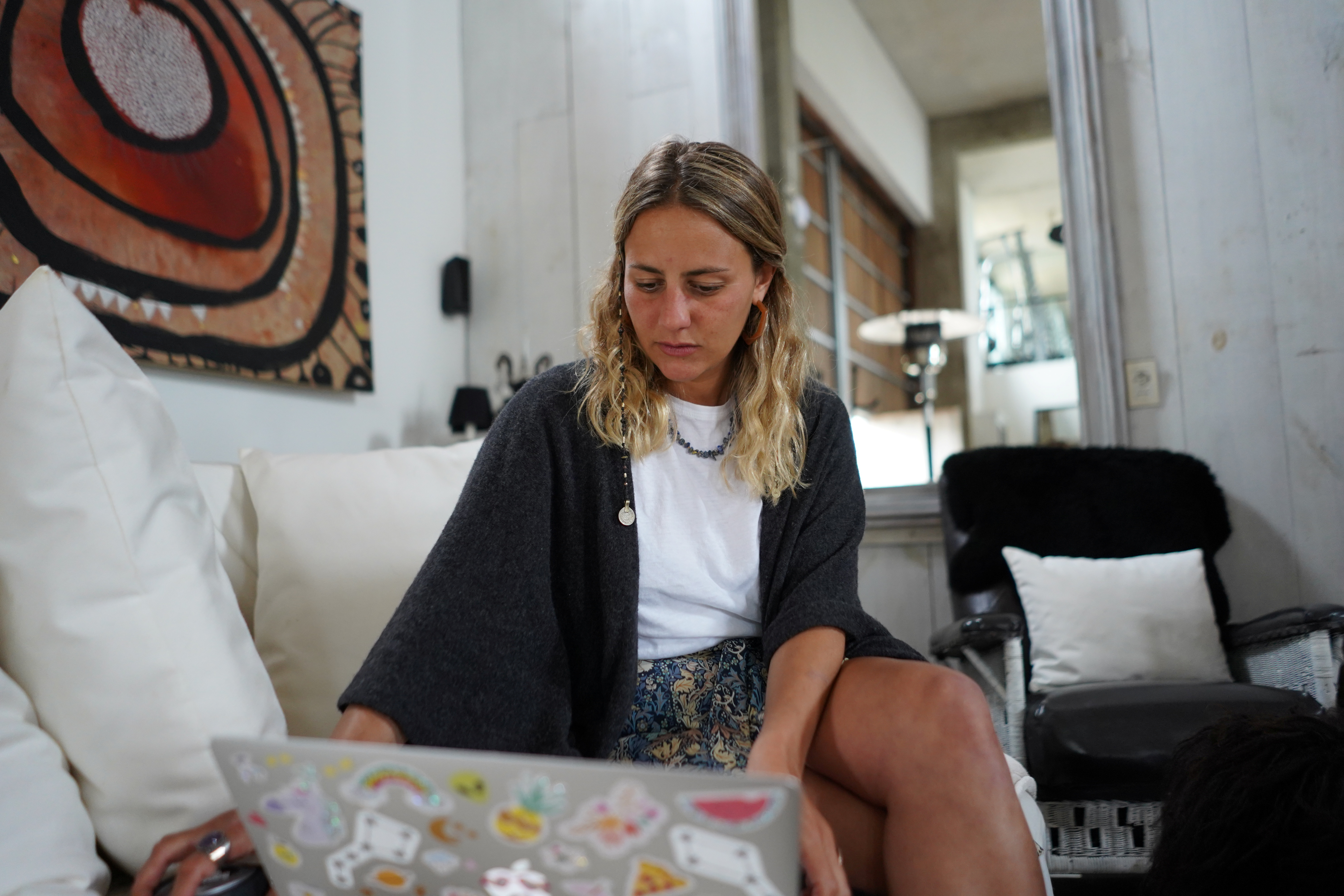 a woman sits at her laptop in a home setting