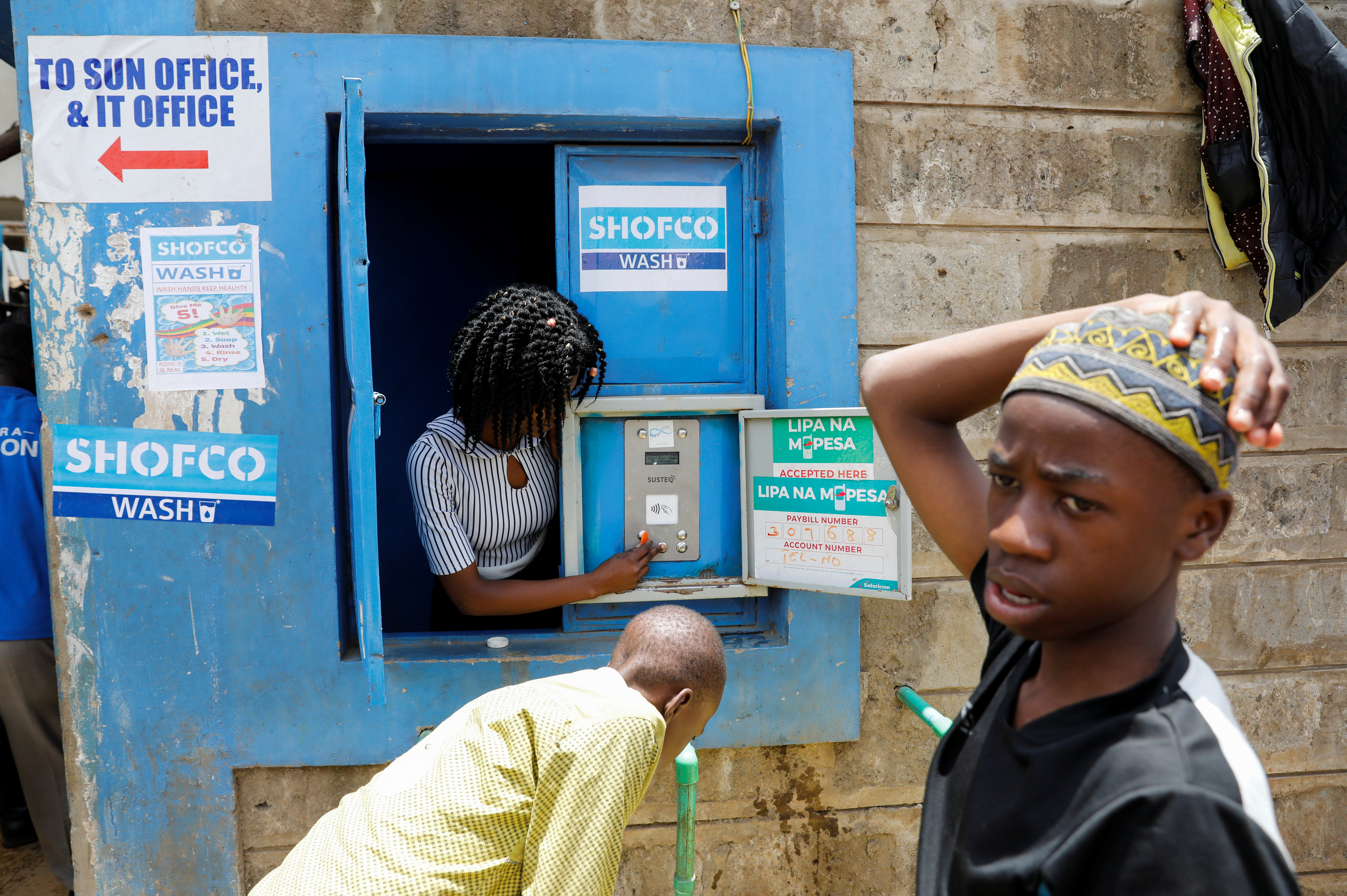 An employe of community organisation Shining Hope for Communities (SHOFCO) activates a water selling machine at a in the Kibera slum in Nairobi, Kenya, March 18, 2020.