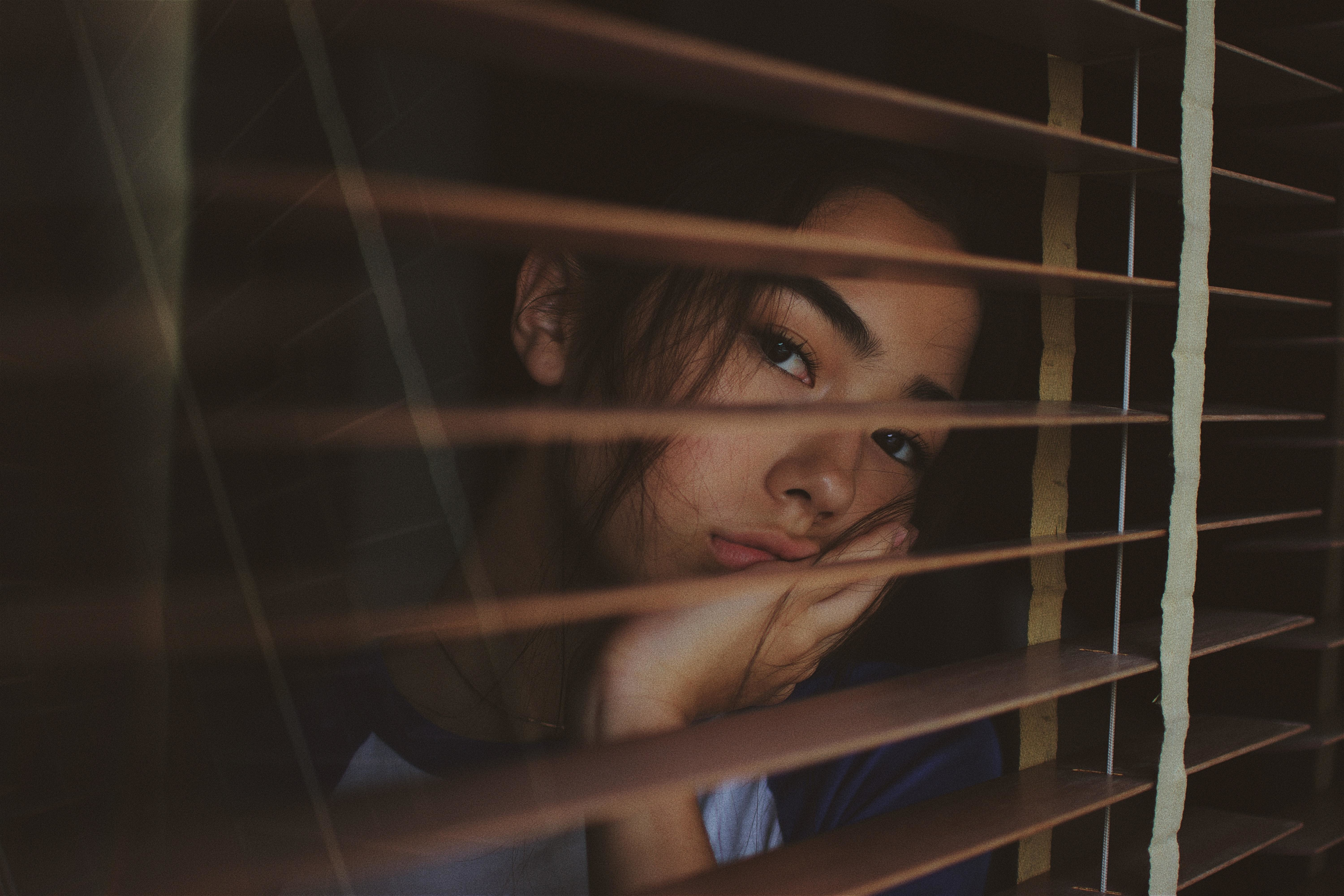 sad girl looking out of window showing how COVID-19 pandemic affects mental health